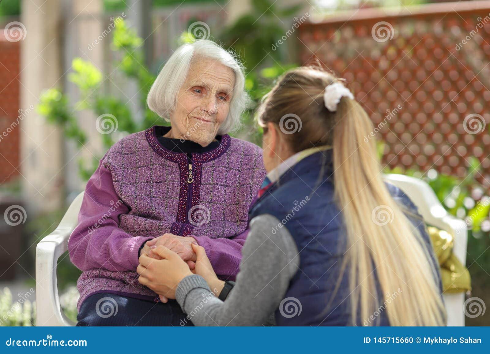 Umfassende alte Gro?mutter der jungen attraktiven Frau im Freien Weibliche - Generationen - Liebe