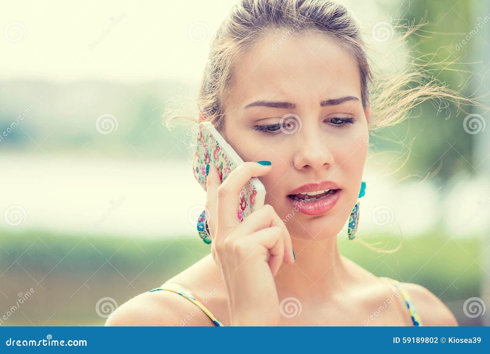 Umgekippte traurige, skeptische Frau, die am Telefon spricht