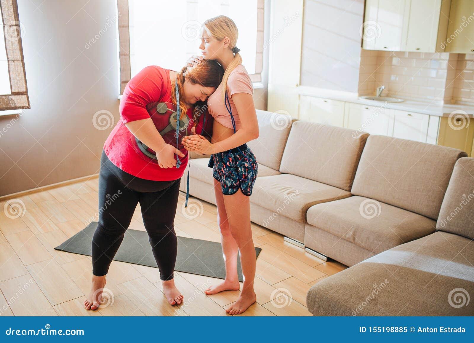 Umgekippte unglückliche junge überladene Frau, die zum dünnen Modell und zum Schreien sich lehnt Sie hält Gewichtsskala in den Hä