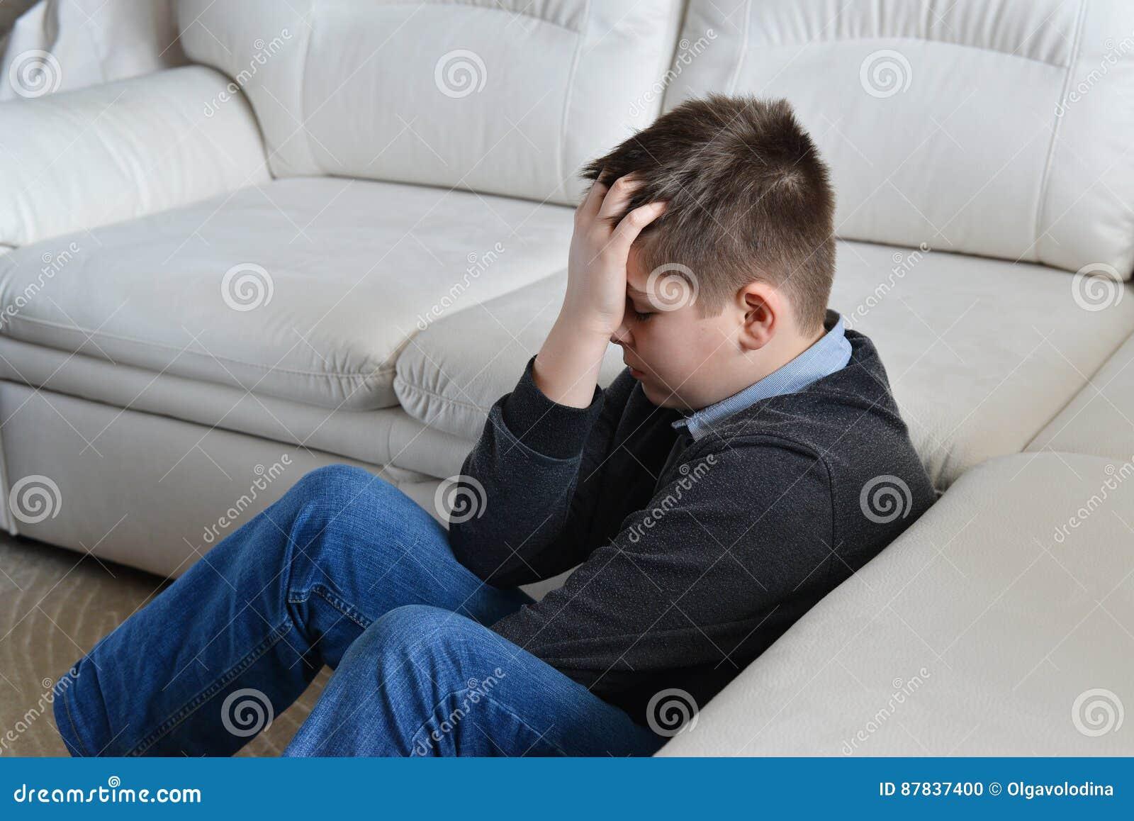 Umgekippter Jugendlicher 13 Jahre sitzend nahe Couch und seinen Kopf in den Händen halten