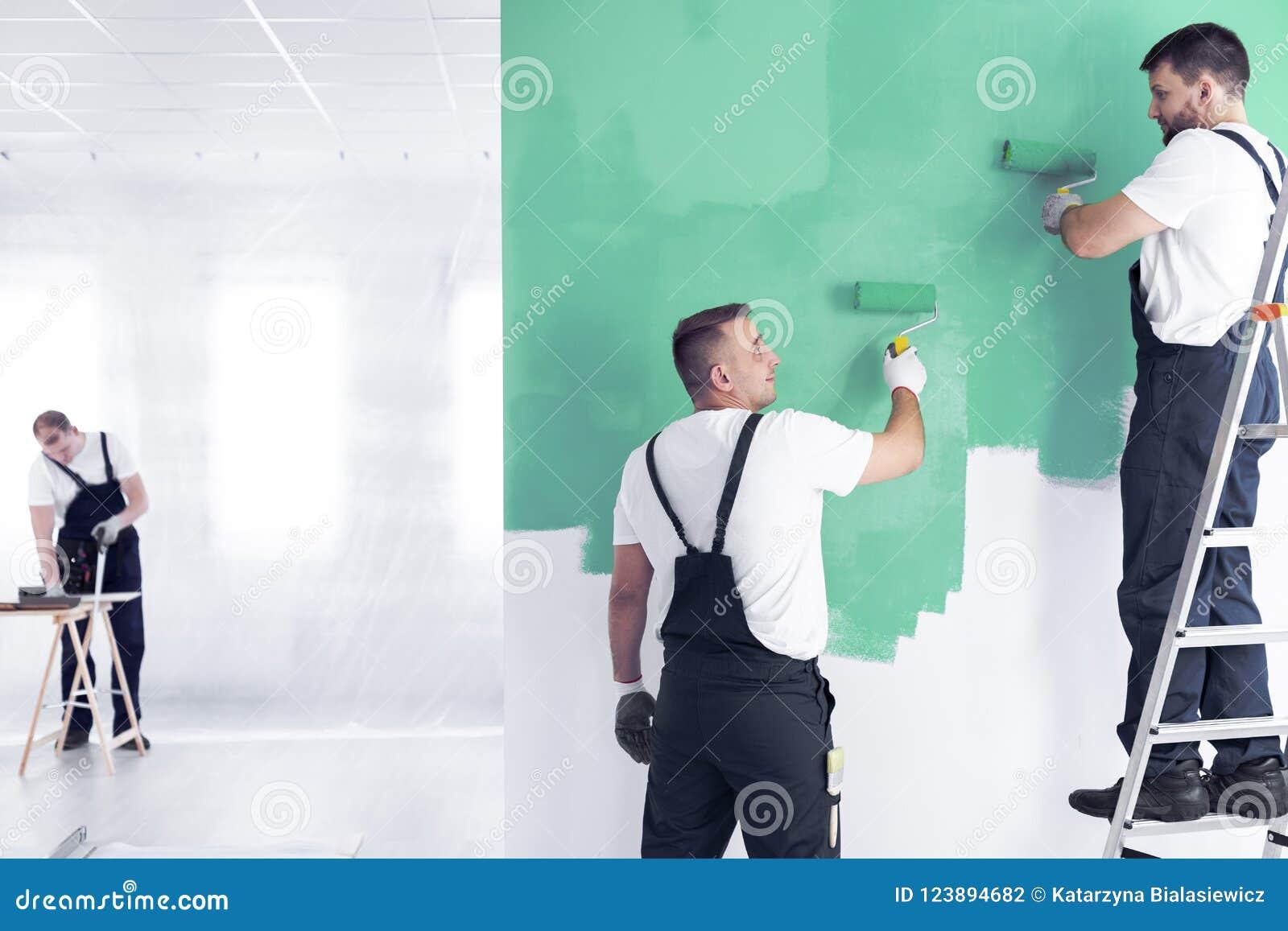 Ummauern Sie Maler auf einer Leiter und eine Erneuerungsmannschaftsarbeitskraft, die a malt