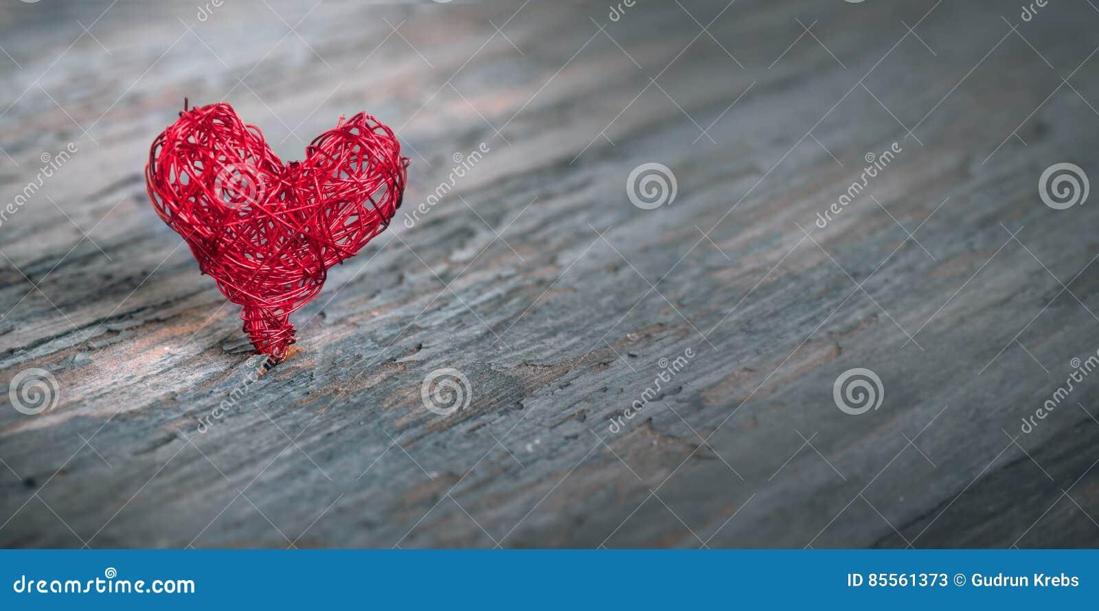 Umsponnenes Herz auf einem alten Holztisch