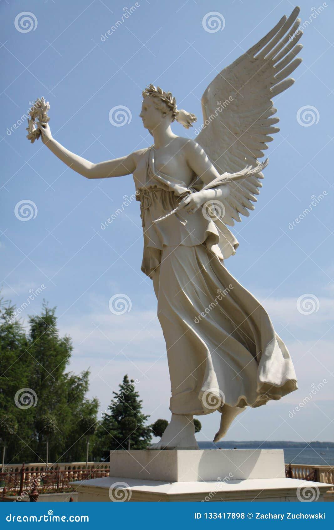 Un ángel en un pedestal cerca del agua