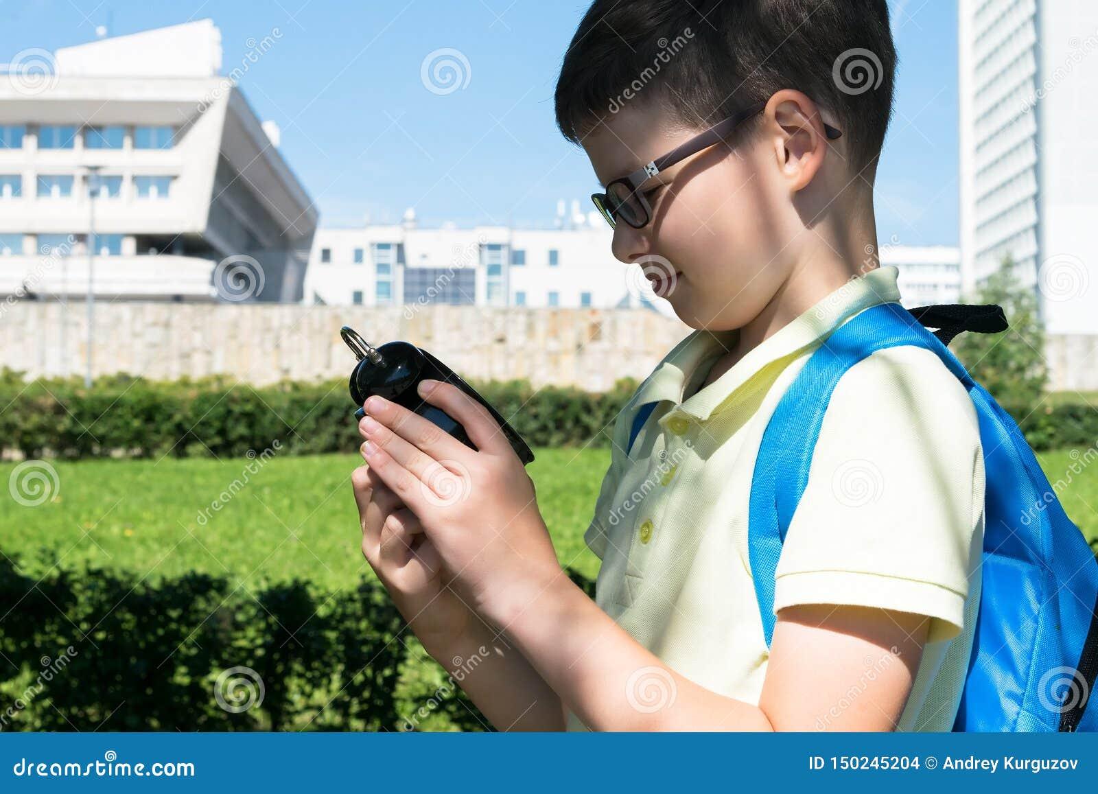 Un écolier dans les regards de parc au réveil, qui prouve que le temps apprend