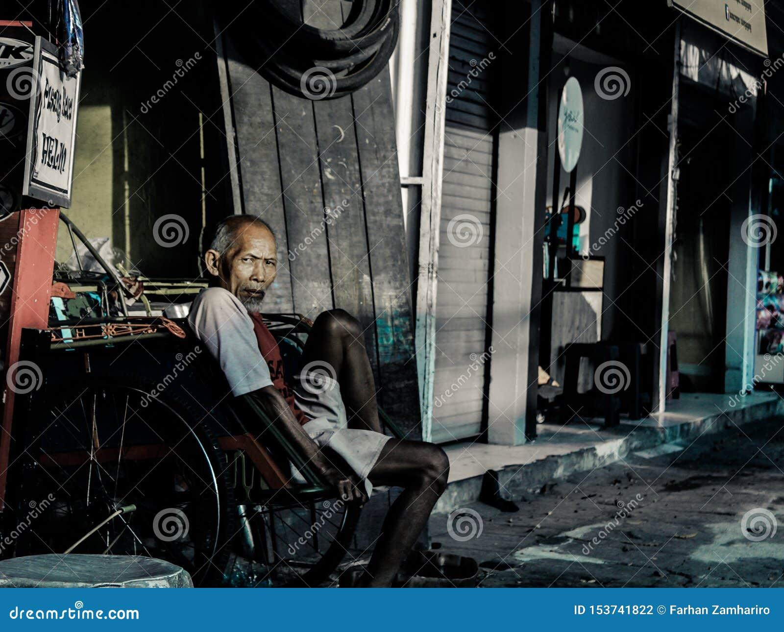 Un abuelo que está descansando mientras que espera a un pasajero