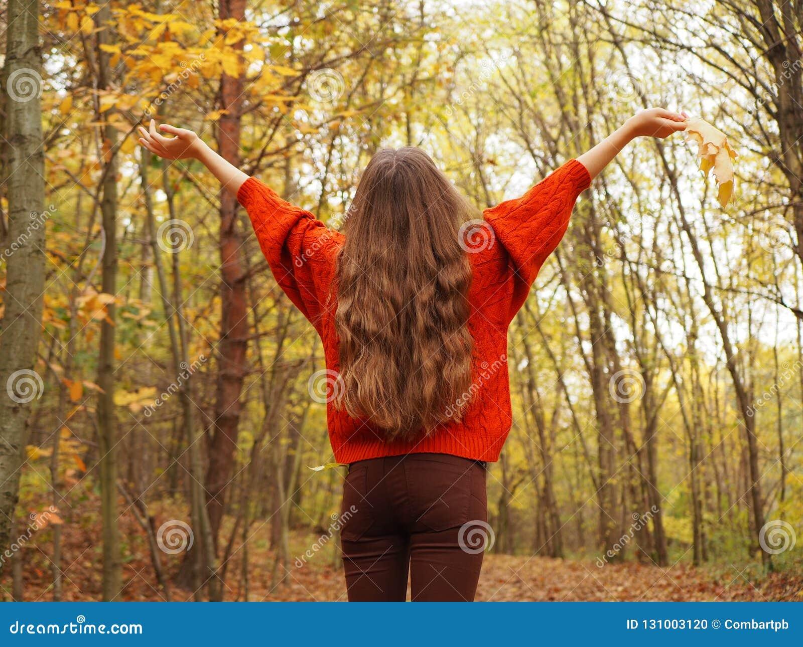 Un adolescent soulevant ses mains avec joie Une fille utilisant le chandail orange et les jeans bruns