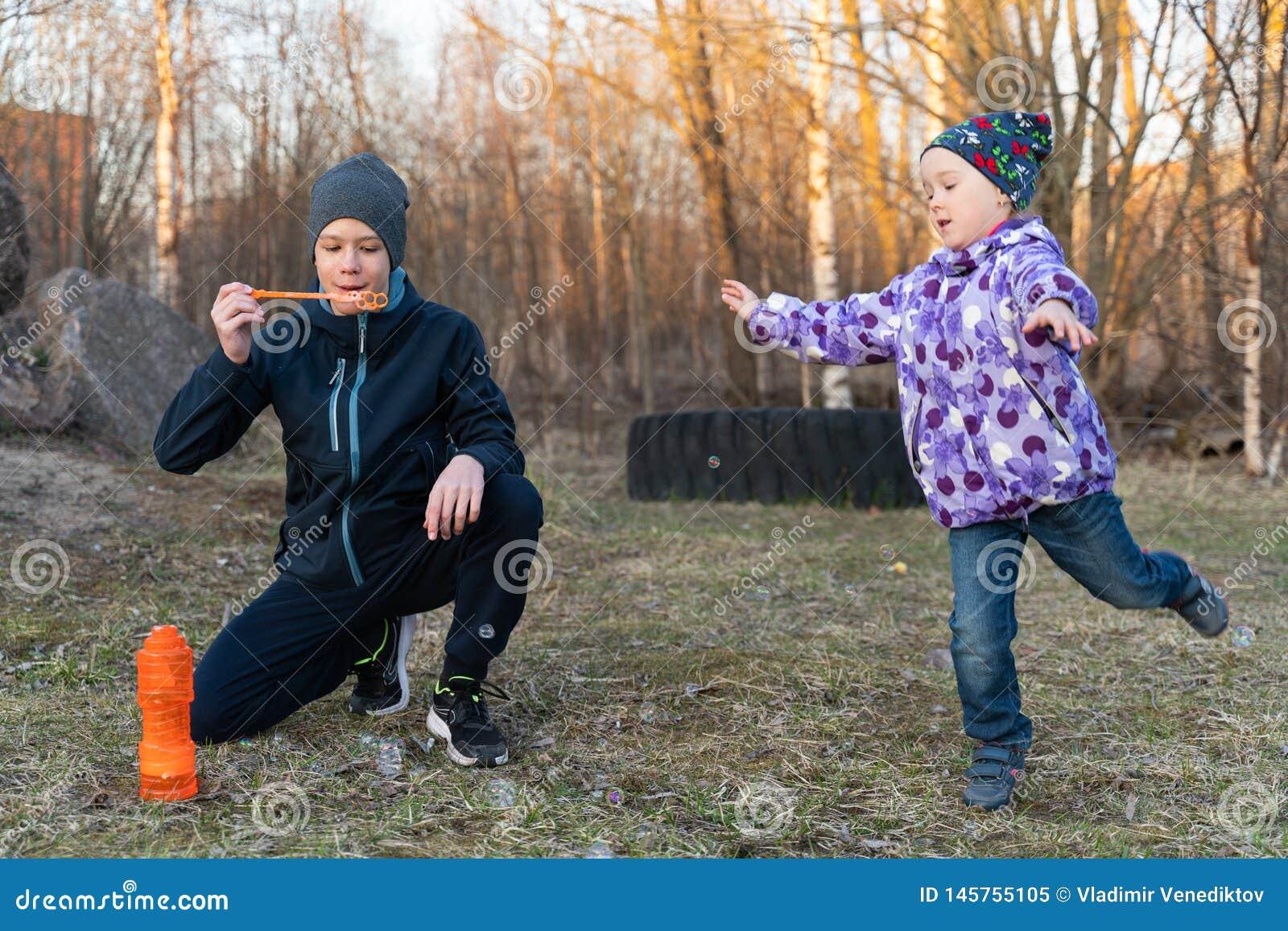 Un adolescente en burbujas que soplan de una chaqueta azul y de un sombrero gris y de una muchacha en el aire abierto Retrato del