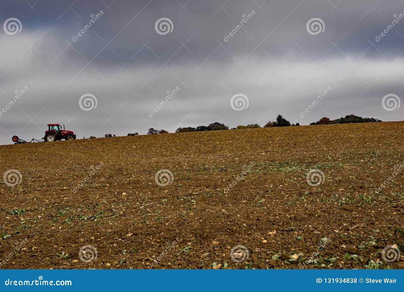 Un agricoltore lavora un campo su una collina in Sheering più basso Essex L autunno tardo e la pioggia è preveduto