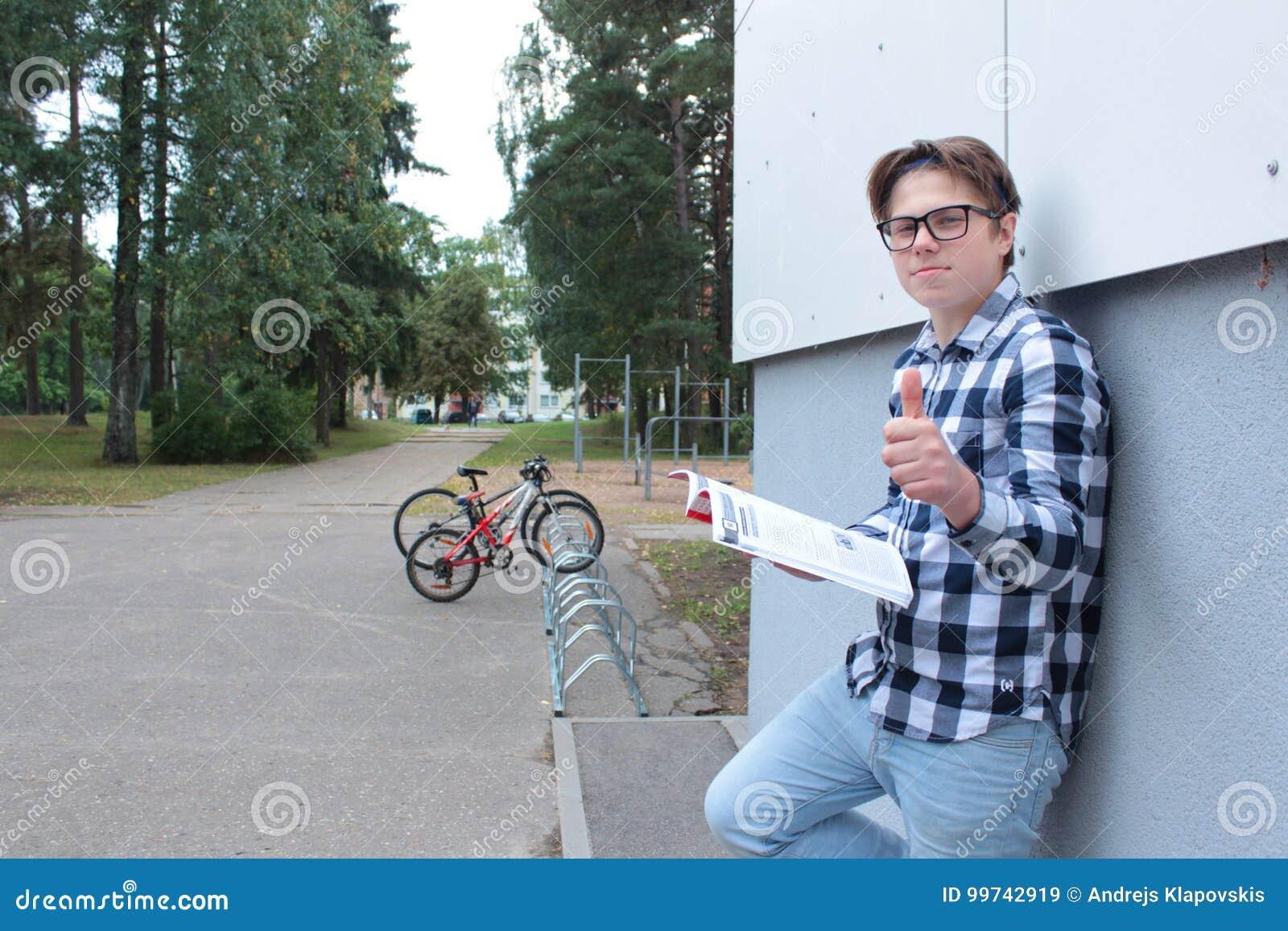 Un alumno o un estudiante del muchacho del adolescente se está sentando en las escaleras, leyendo un libro, los vidrios que lleva