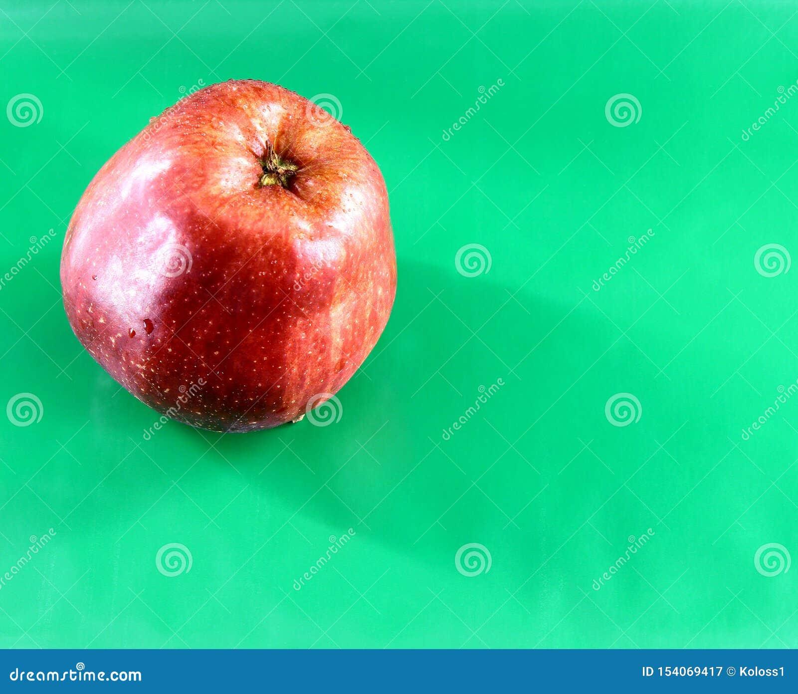 Un Apple rouge frais avec des baisses de l eau sur le fond vert