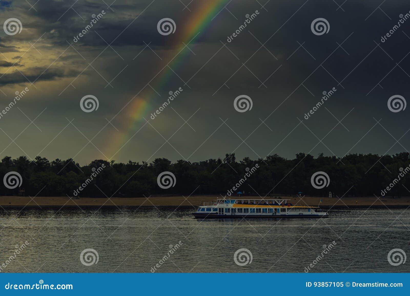 Un arcobaleno da un buio si rannuvola un fiume e una nave del motore