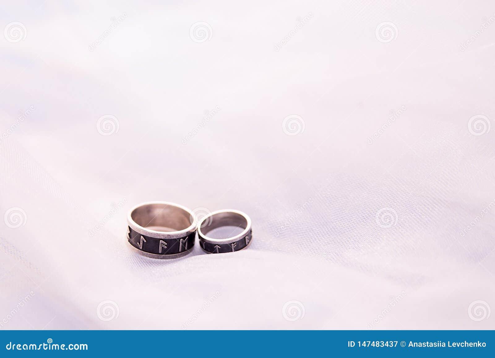 Un argento di due fedi nuziali su fondo bianco con lo spazio della copia anelli con le rune Concetto di amore e del matrimonio