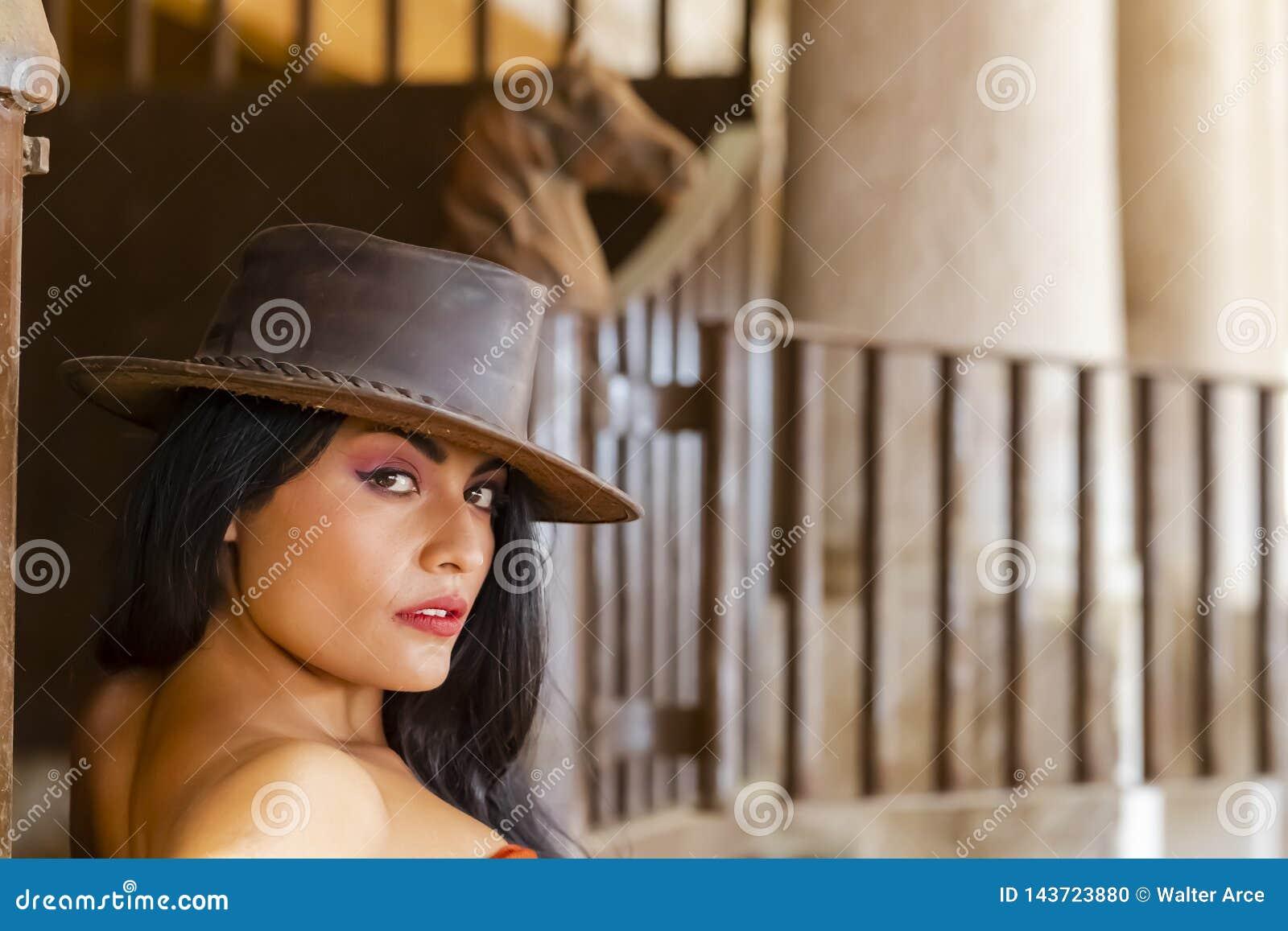 Un aria aperta castana ispana adorabile del cavallo di Poses With A del modello in un ambiente familiare