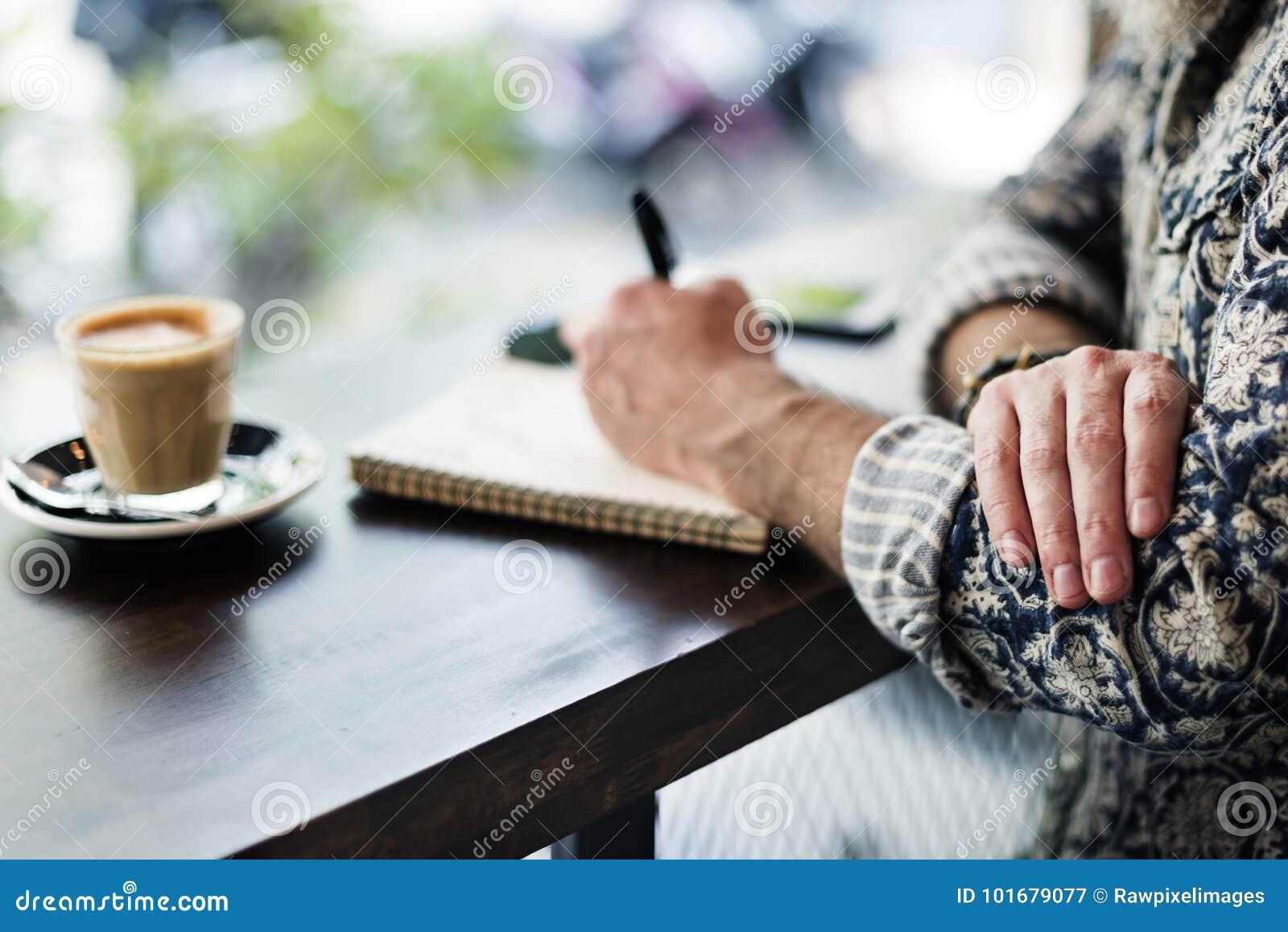 Un autore che fa le note in una caffetteria
