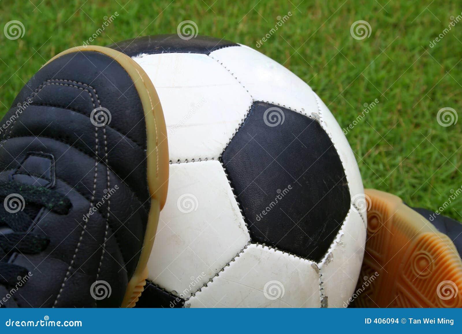 Un balón de fútbol y pares de zapatos