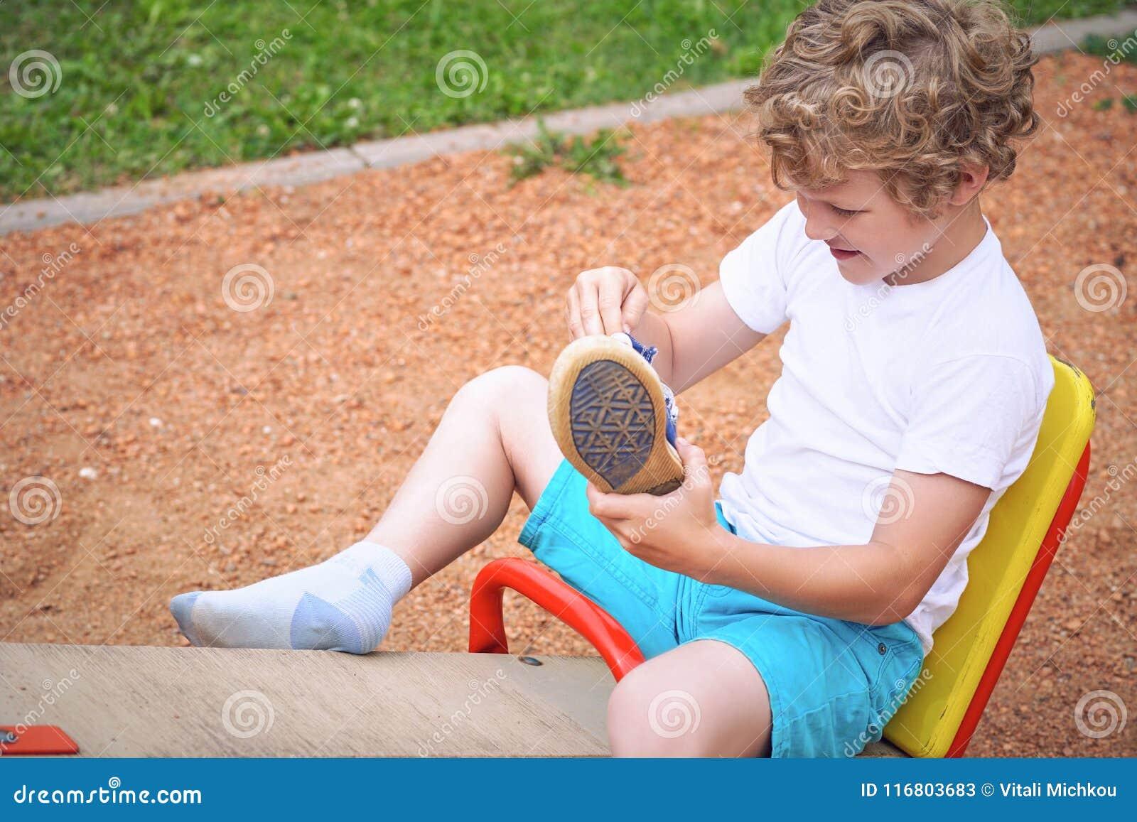 Un bambino piccolo divertendosi gioco sull attrezzatura ad un campo da giuoco