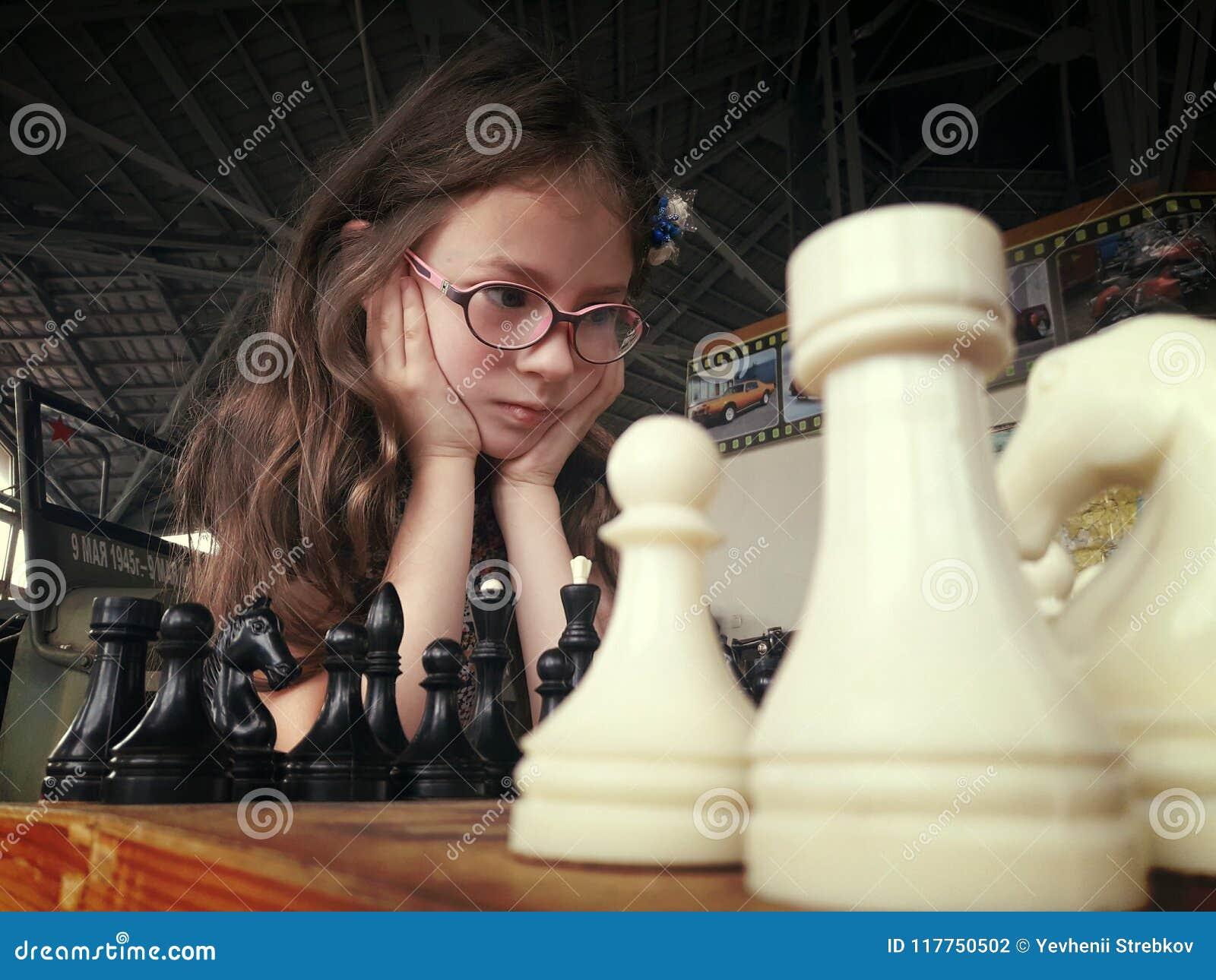 Un bambino in vetri gioca di scacchi