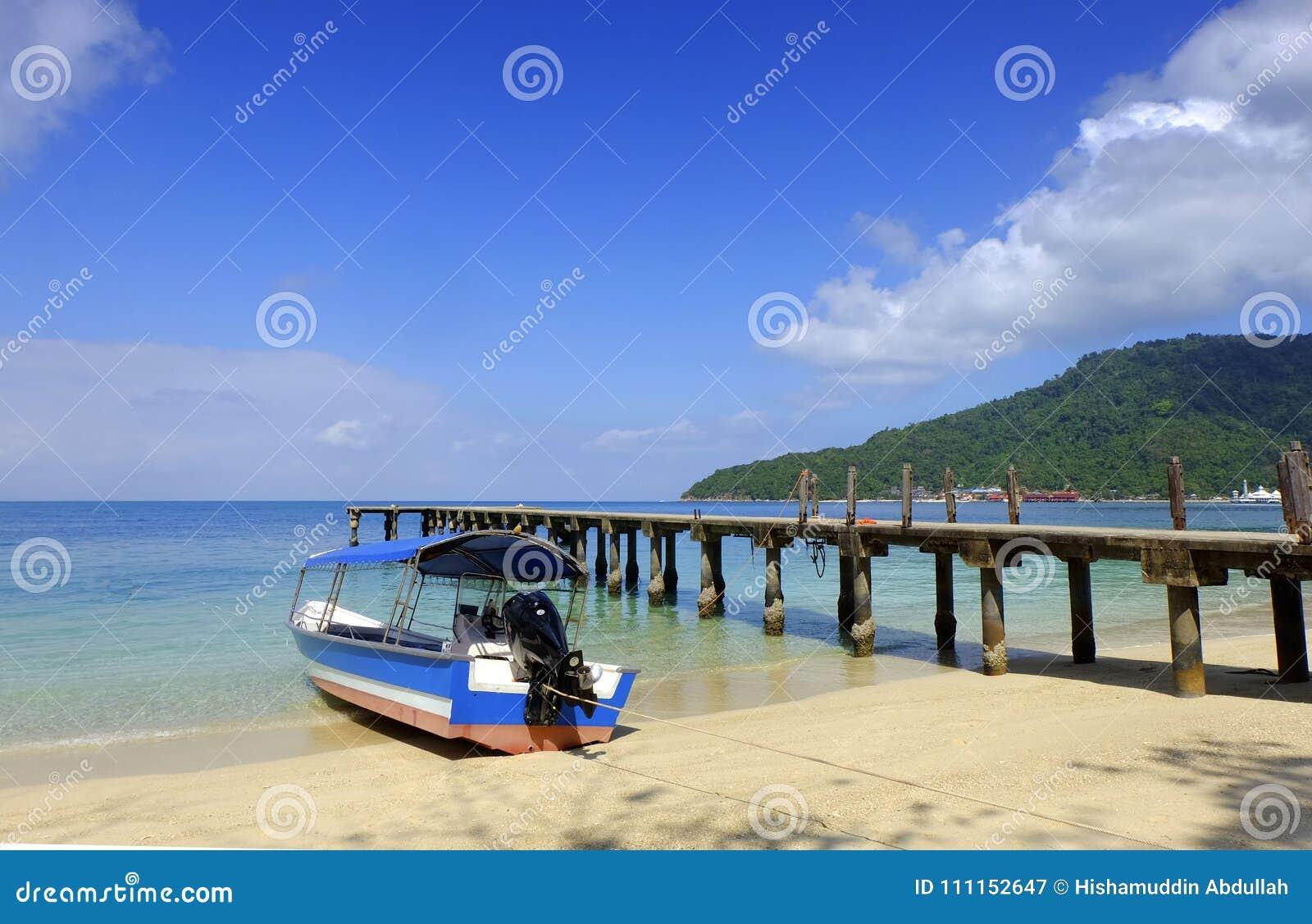 Un barco con un paisaje del cielo azul en la isla perhentian