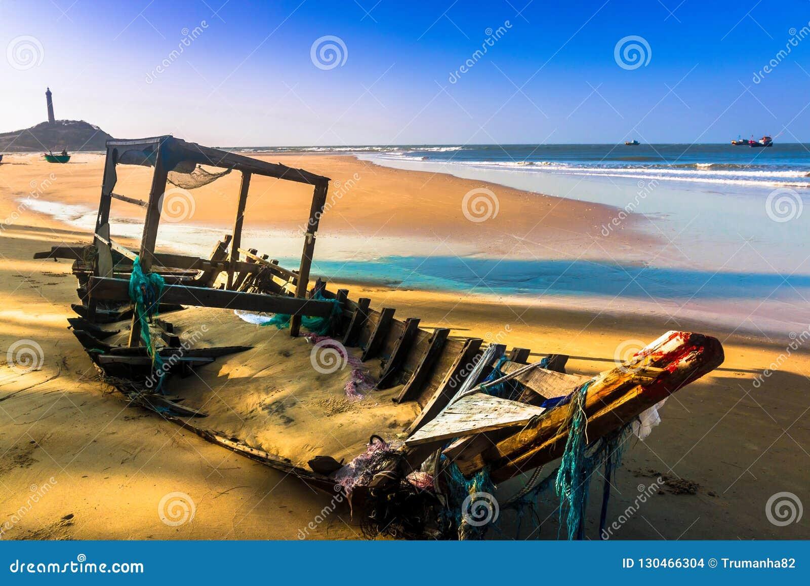 Un barco de pesca viejo quebrado en Sandy Beach en el cabo de KE GA, Binh Thuan, Vietnam