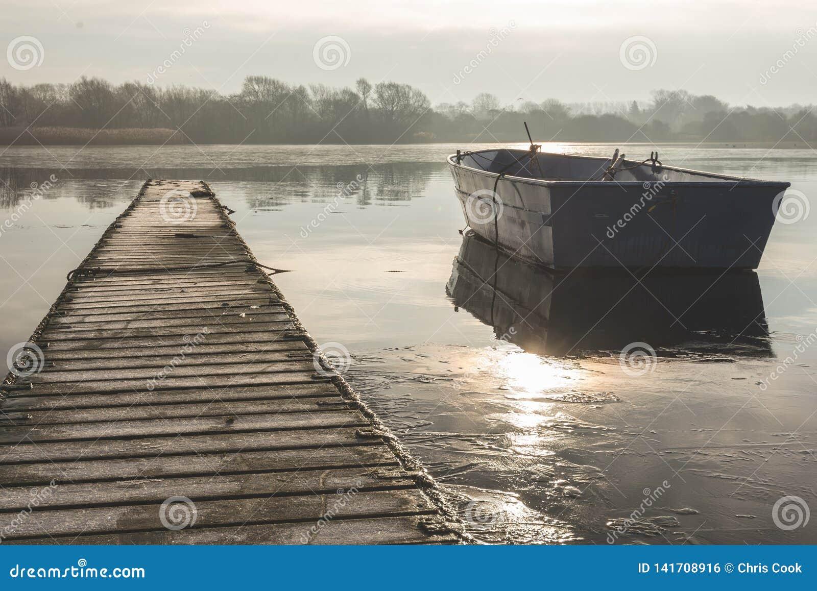 Un barco que rema flota a la deriva en un lago congelado al lado de una calzada vacía