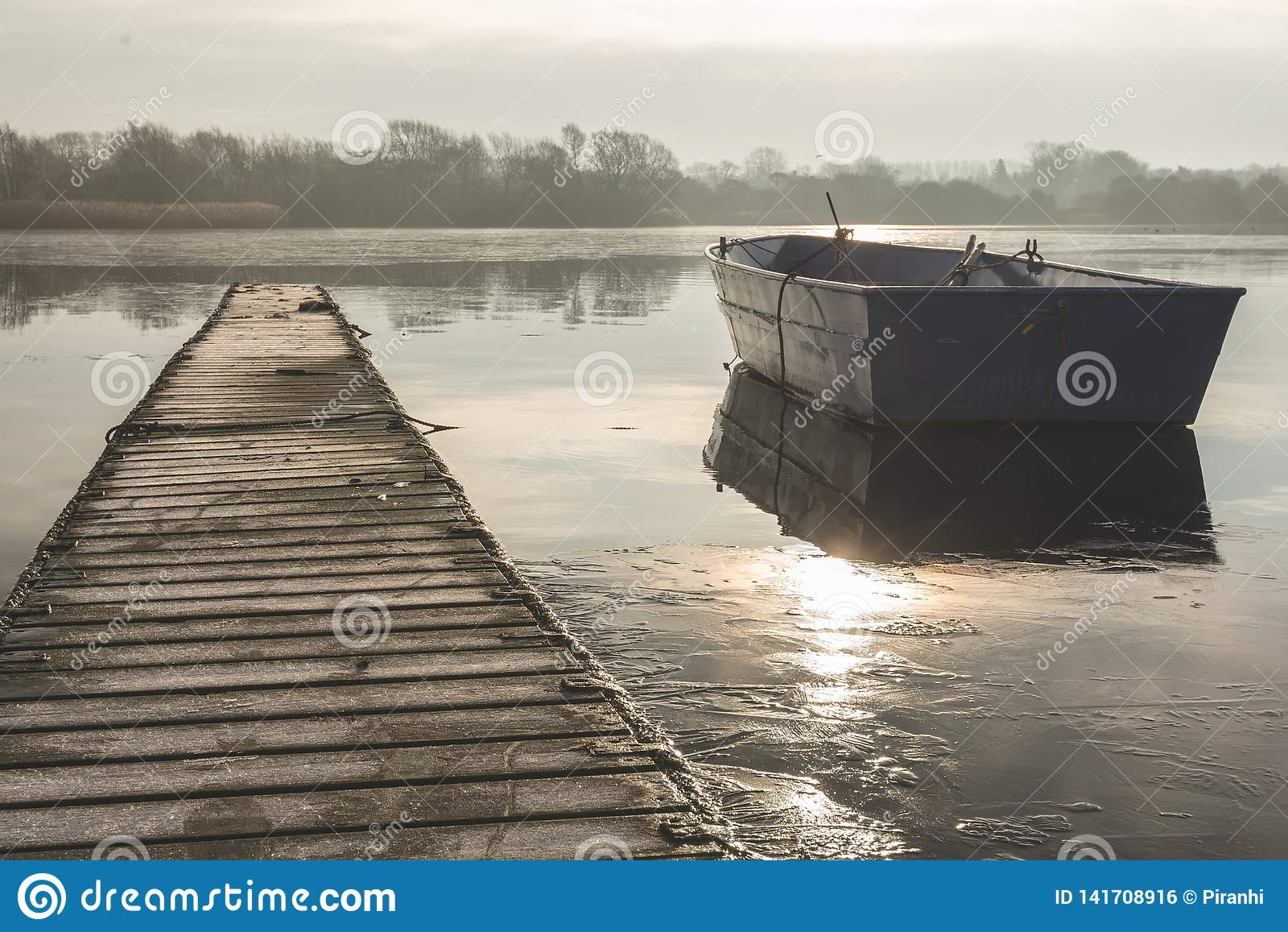 Un bateau à rames flotte à la dérive sur un lac congelé près d un passage couvert vide