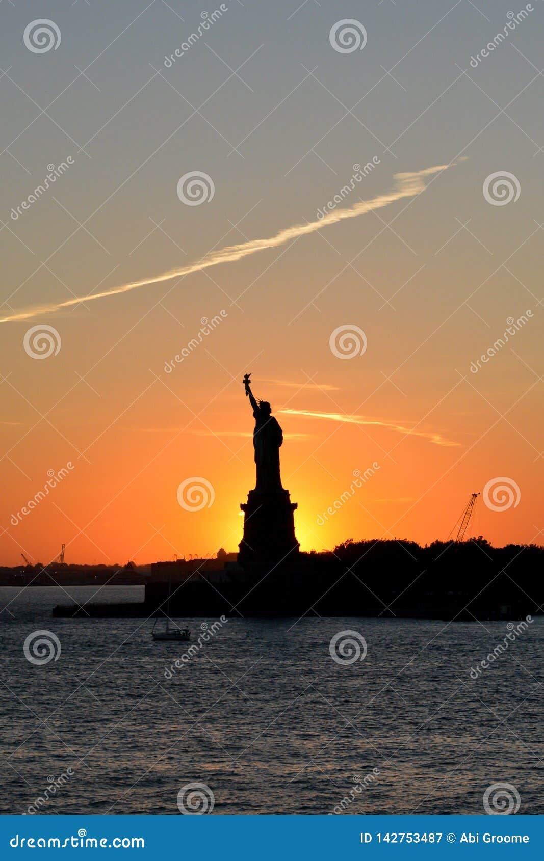 Un beau coucher du soleil avec une statue silhouettée contre le ciel
