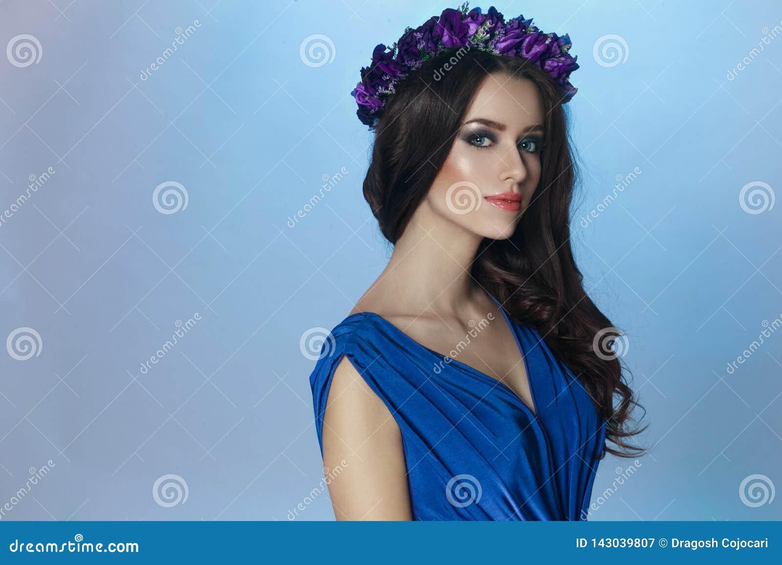 Un beau modèle de brune avec composent et de longs cheveux et couronne bouclés avec des fleurs de violettes sur sa tête
