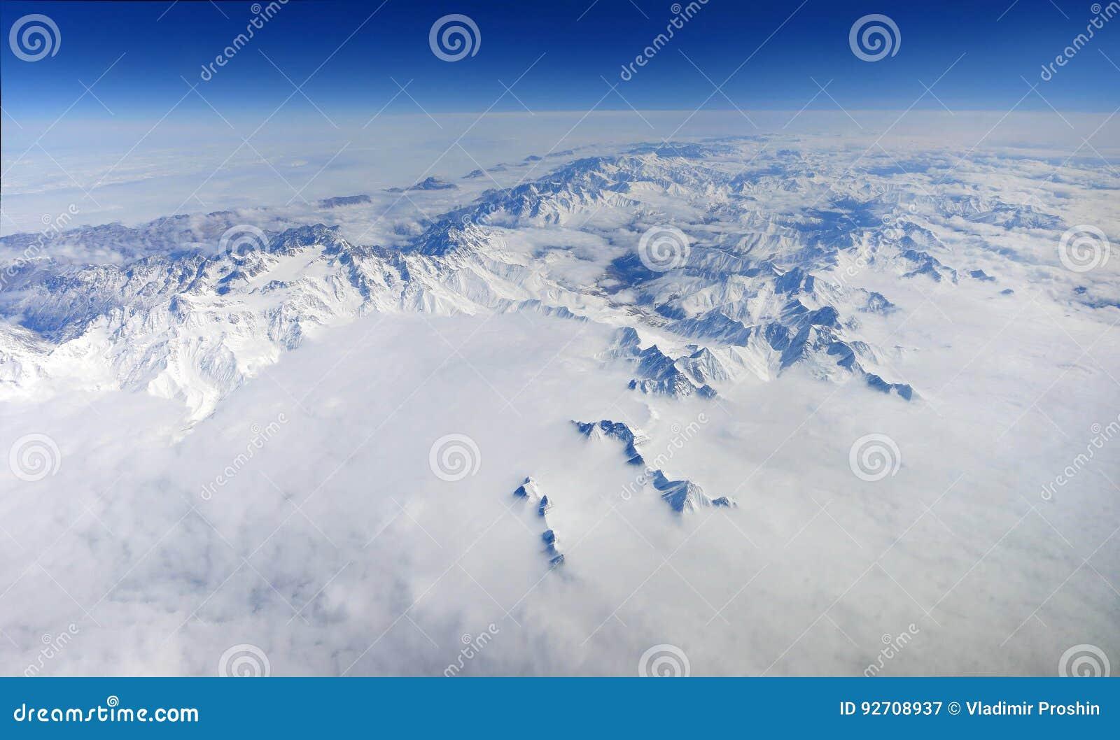 Un beau panorama des montagnes couronnées de neige avec des nuages