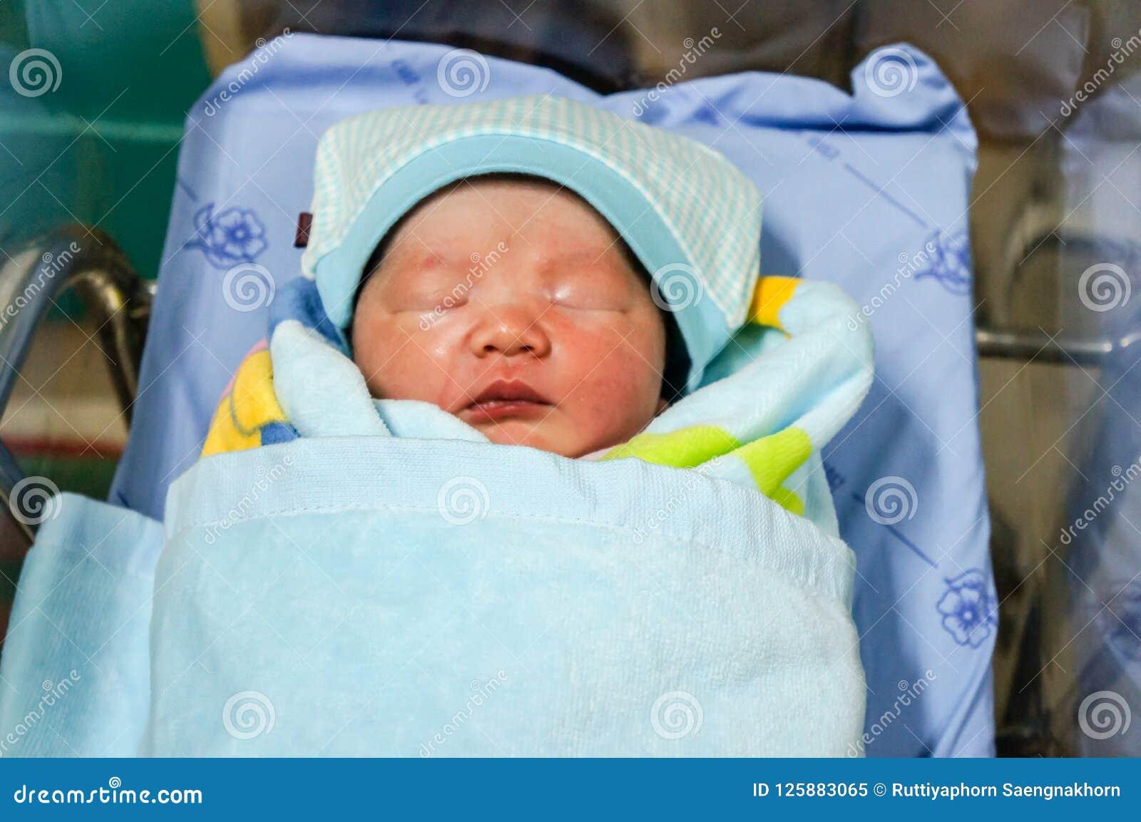 Un bebé asiático, sueño lindo de la cara bien con la cubierta la manta