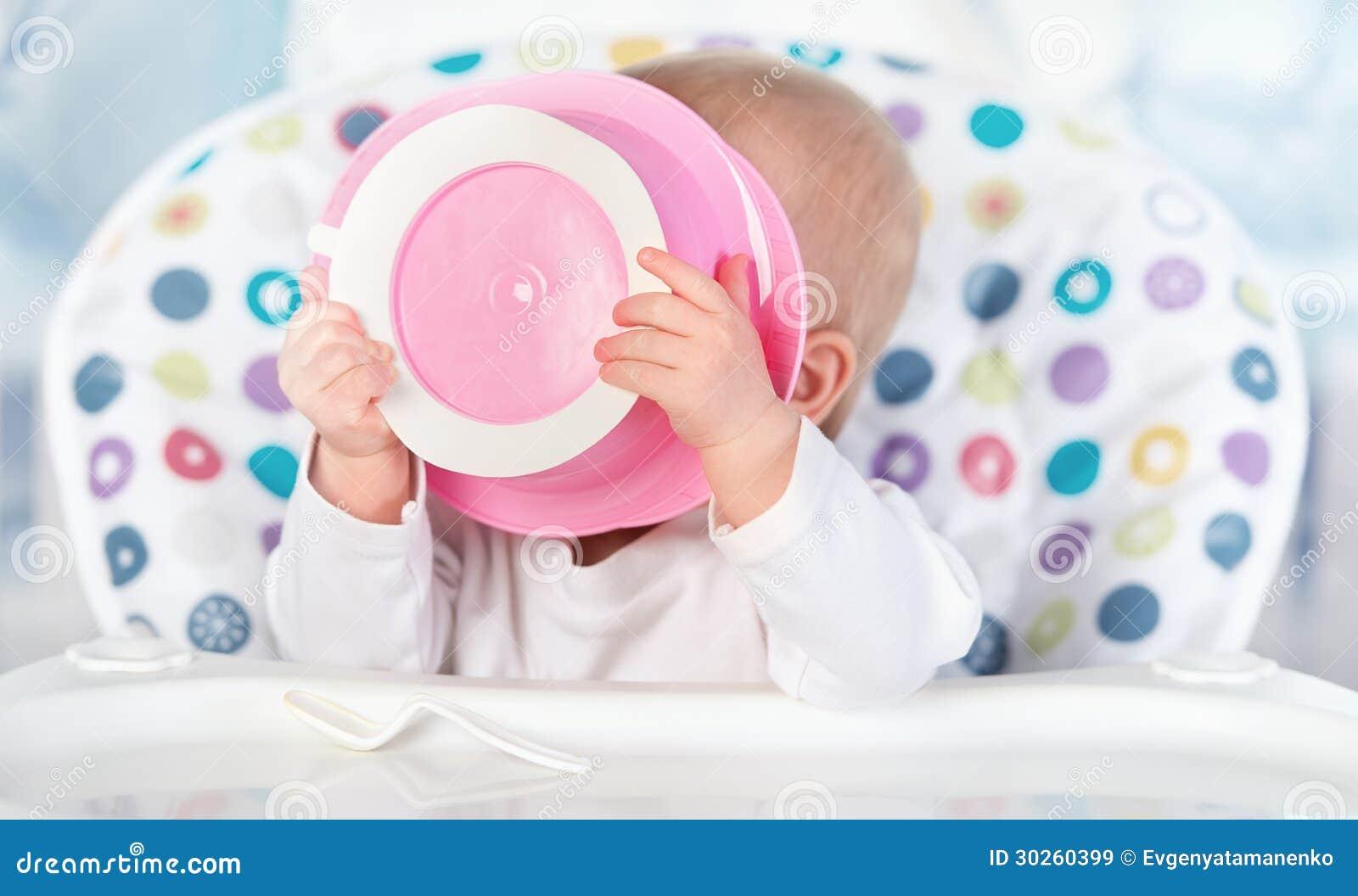 El bebé divertido está comiendo de la placa rosada