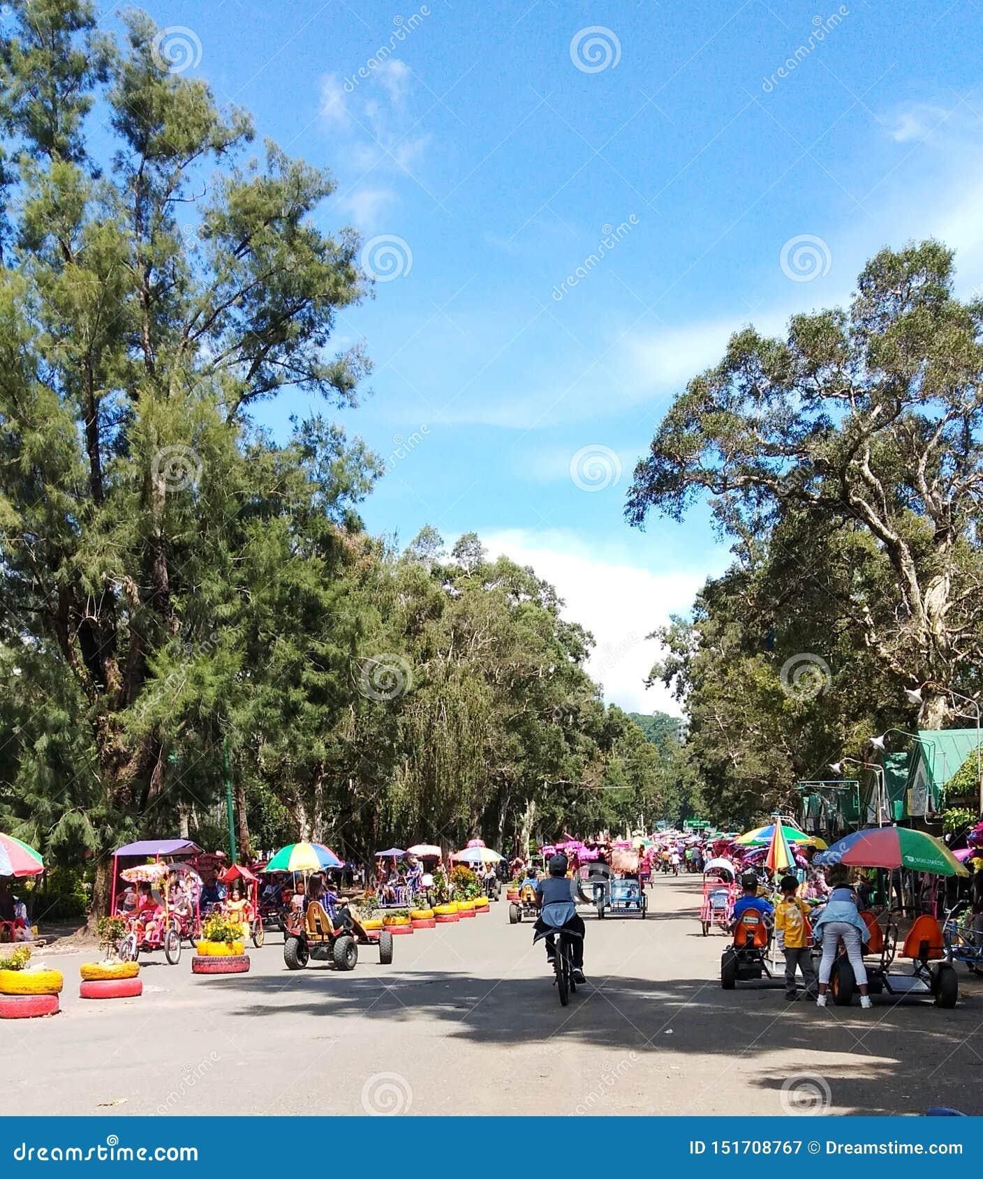 Un bello giorno a Burnham Park in Baguio City Bambini che prendono un giro della bici