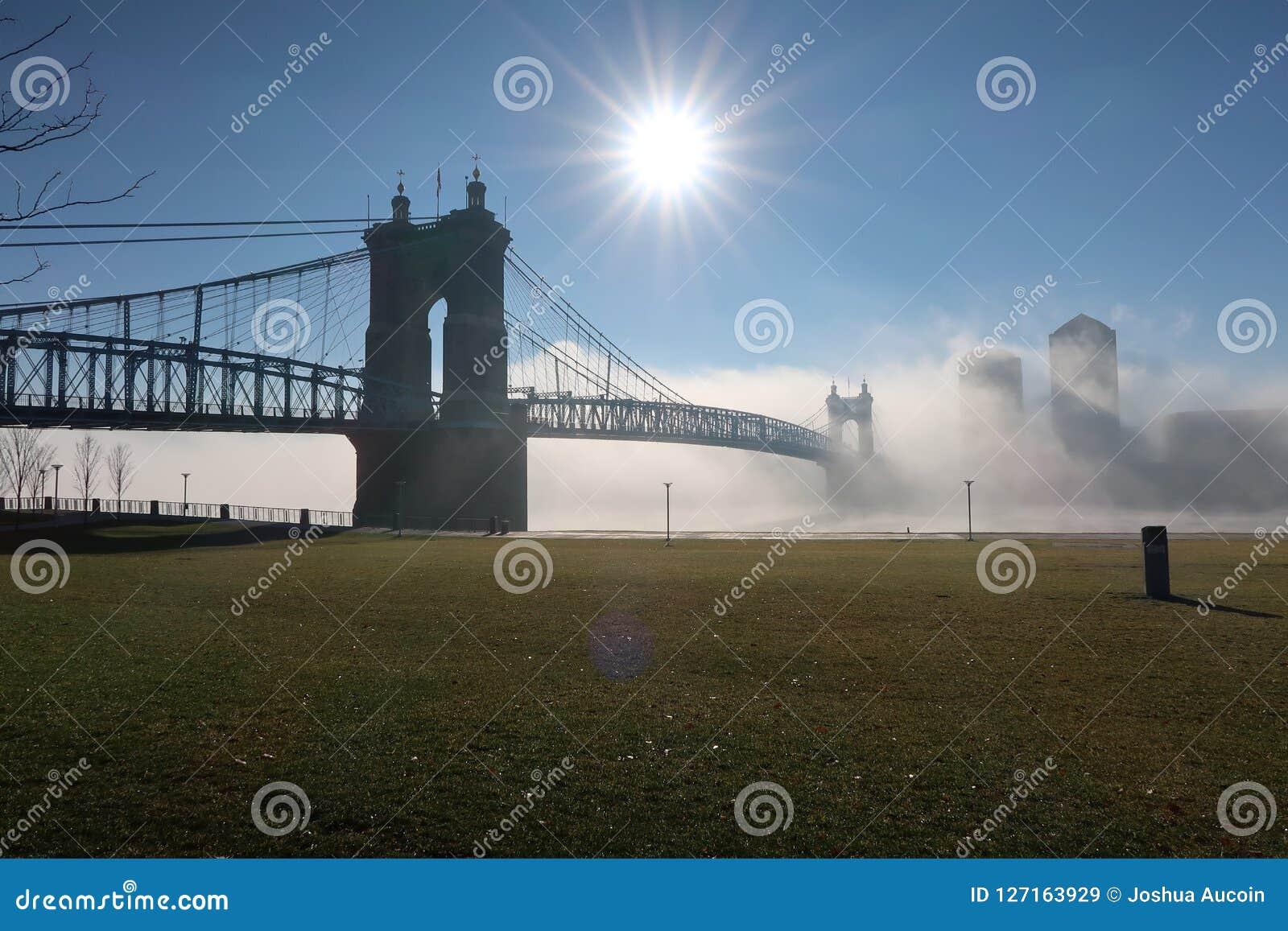 Un bello ponte della città si siede nella nebbia pesante di mattine