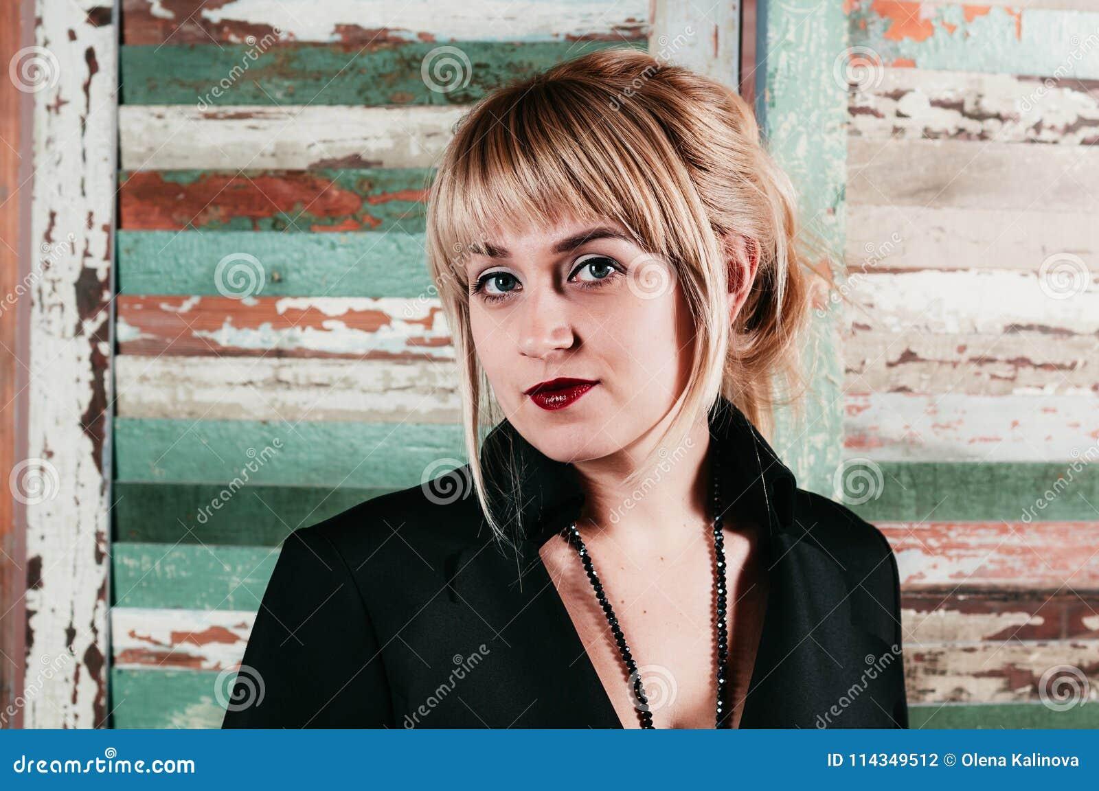 Un blonde imponente en el vestido negro, sonriendo