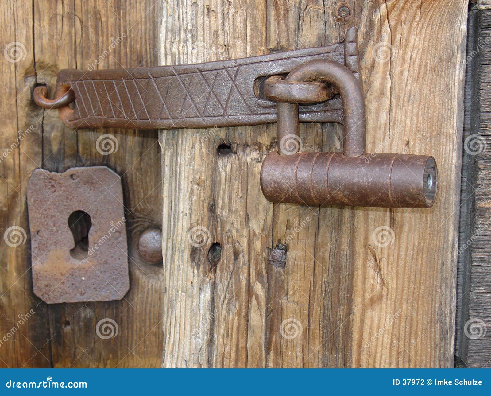 Un bloqueo viejo del hierro en un viejo woodhouse