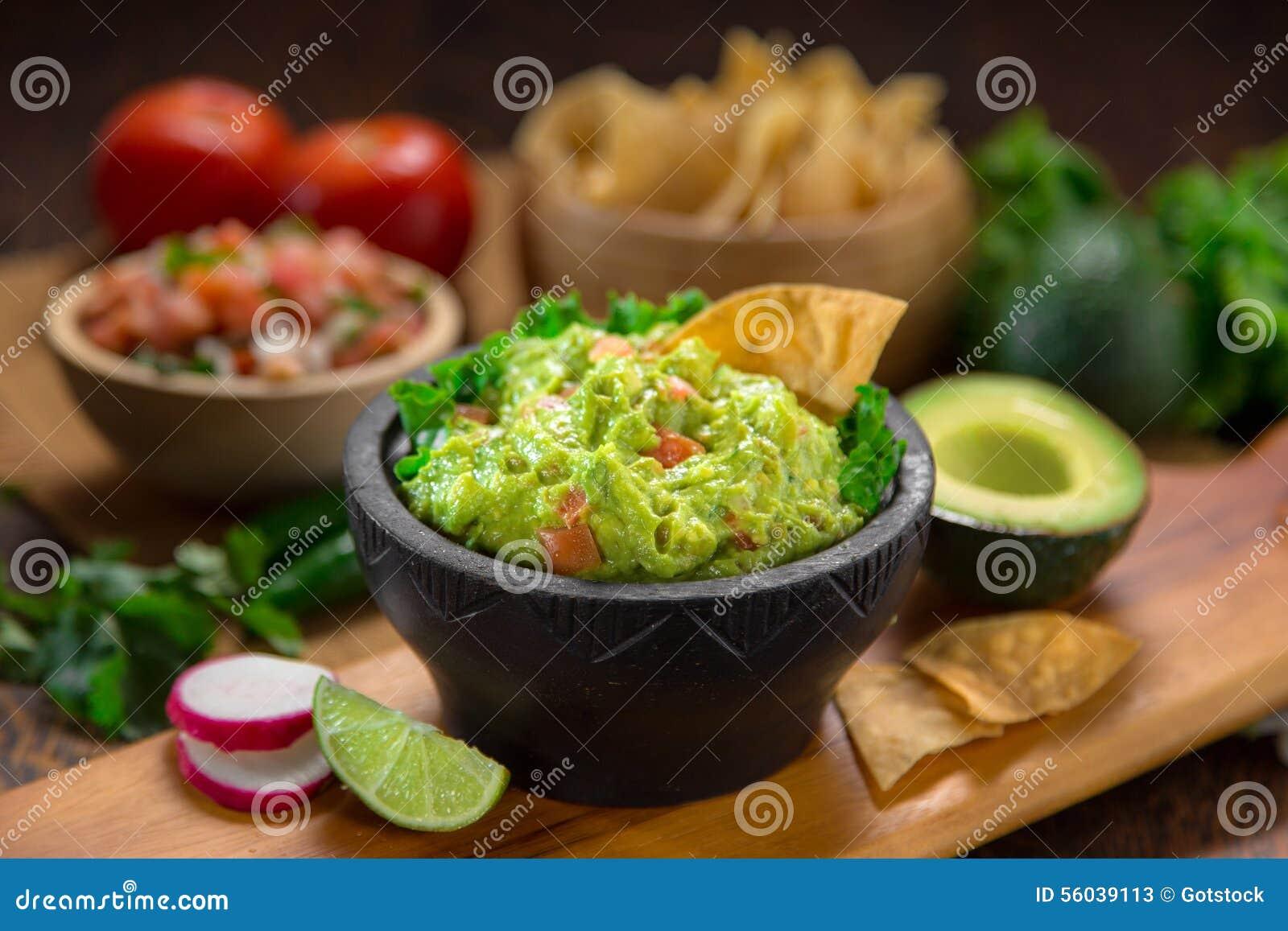 Un bol délicieux de guacamole à côté des ingrédients frais sur une table avec les frites et le Salsa de tortilla