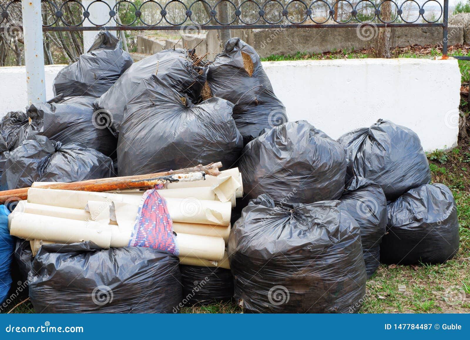 Un bon nombre de sacs de déchets noirs près de la barrière