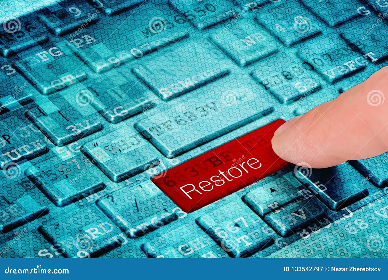 Un botón de restauración rojo de la prensa del finger en el teclado digital azul del ordenador portátil