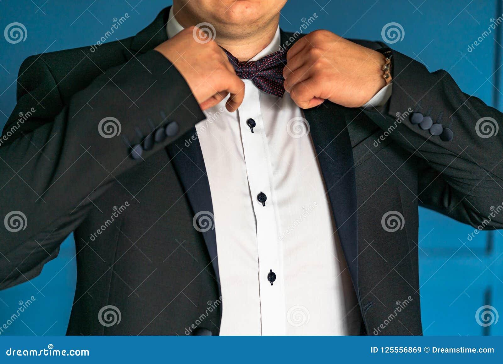 Un caballero en lujoso en una chaqueta negra y una camisa blanca corrige la corbata de lazo al lado de sus manos