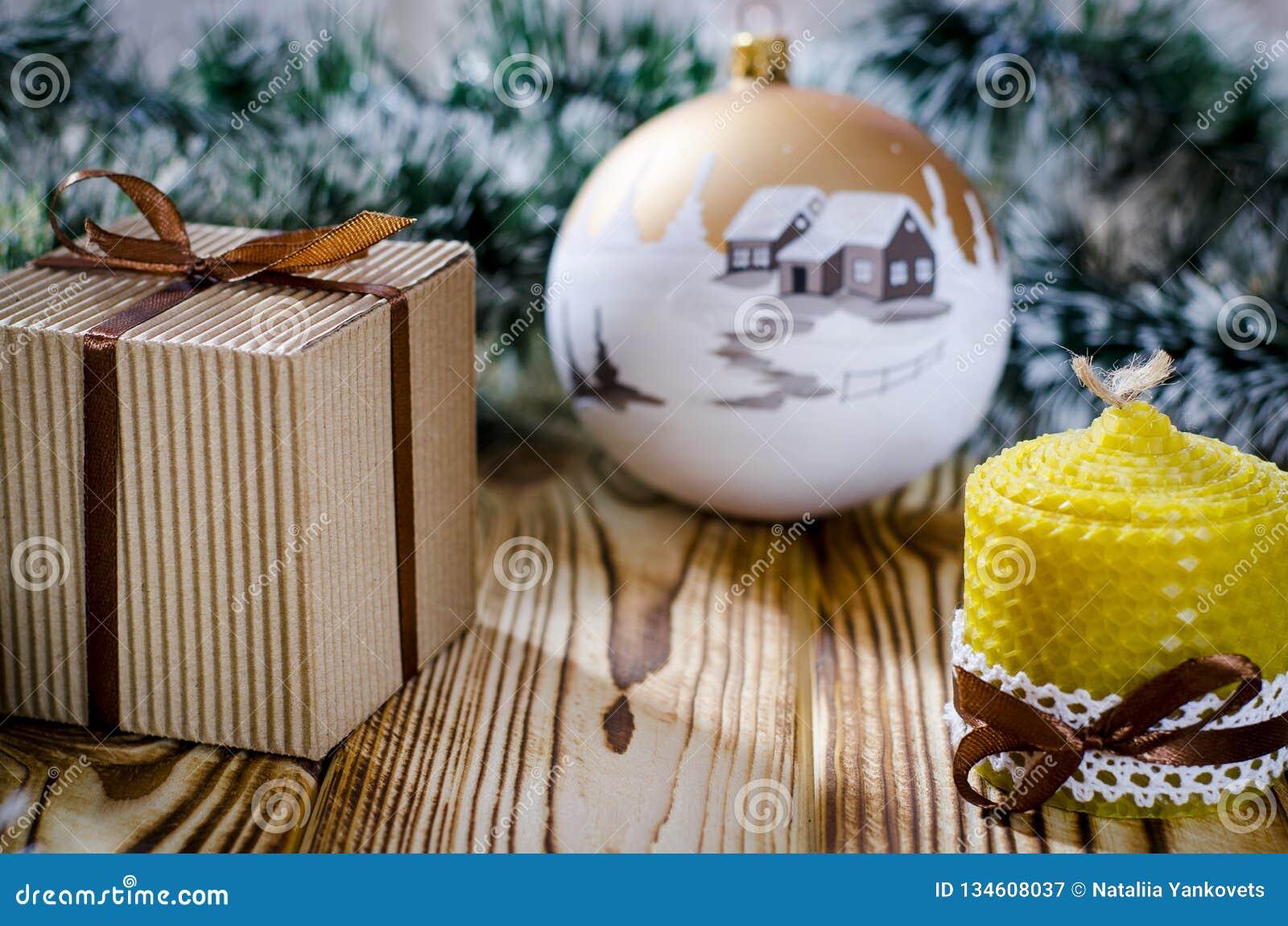 Un cadeau s étend sur une table en bois à côté d une bougie, des cônes et d un ange dans la perspective des décorations de Noël