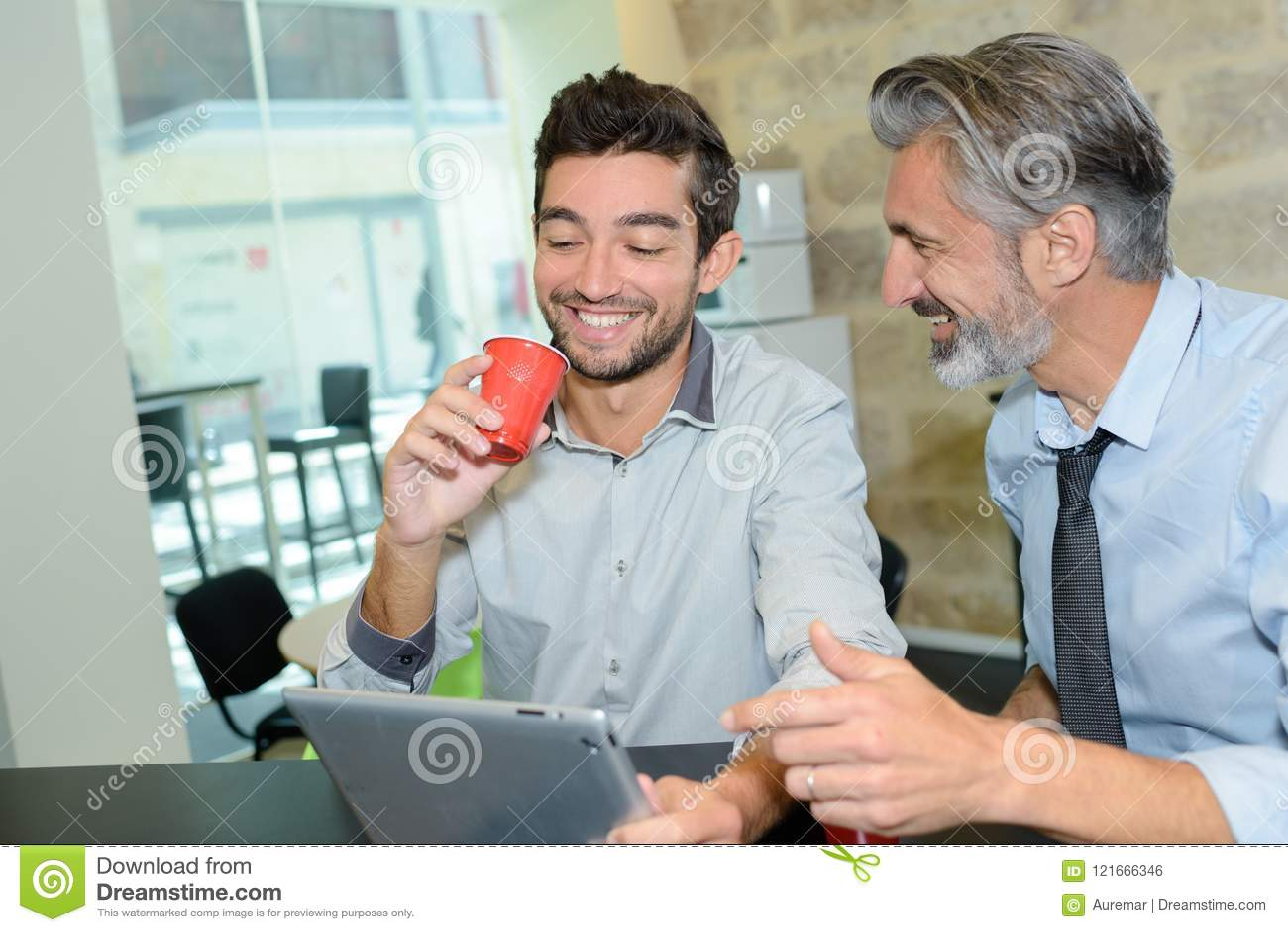 Un caffè di due uomini d affari che incontra concetto senza fili della compressa