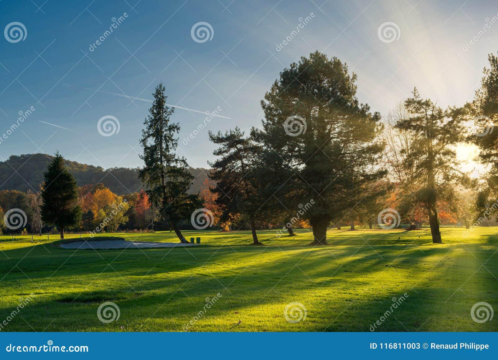 Un campo e un cielo blu verdi di golf in autunno al tramonto