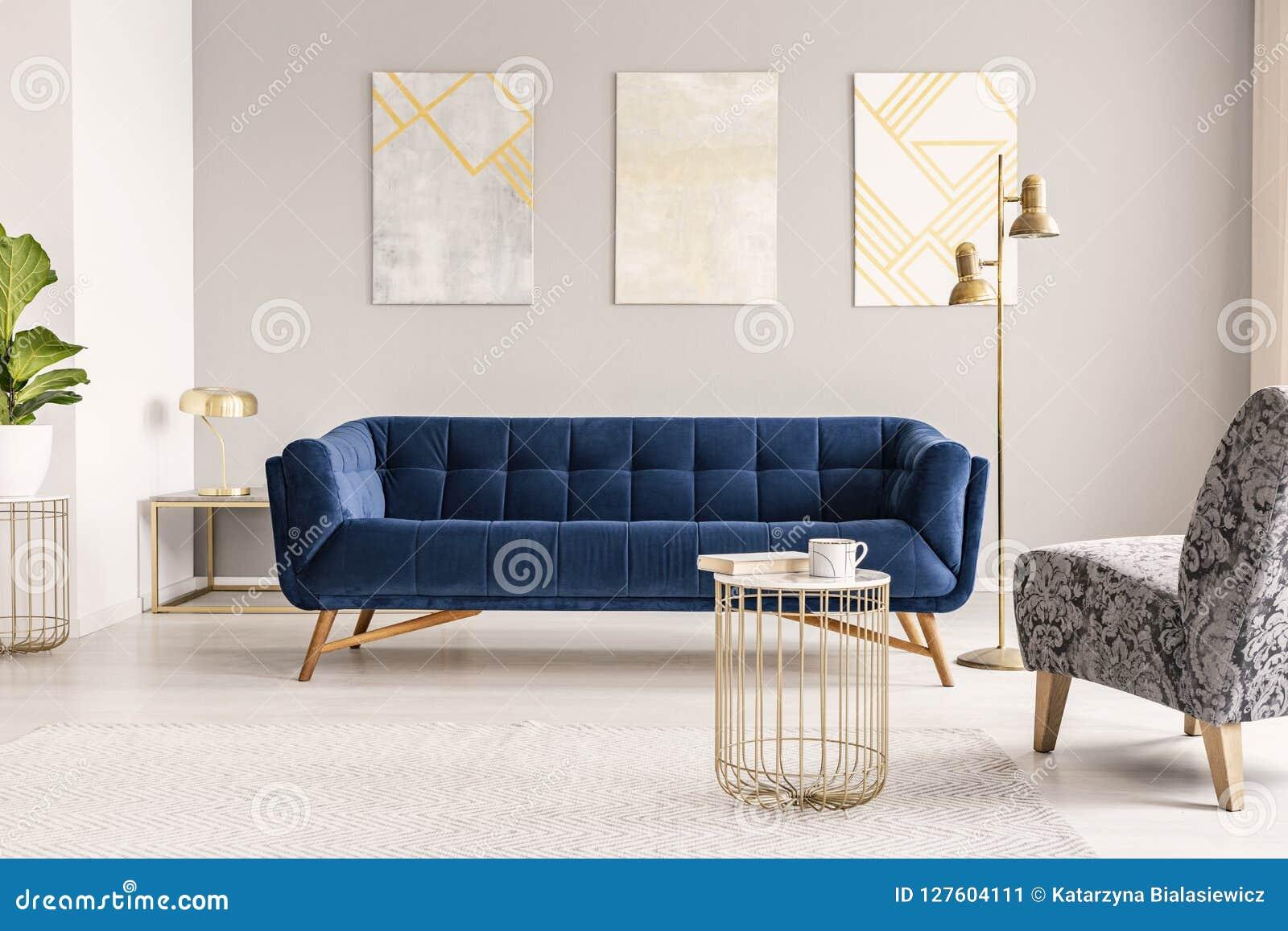 Un canapé azul marino del terciopelo contra una pared gris con las pinturas modernas en un interior vacío de la sala de estar Fot