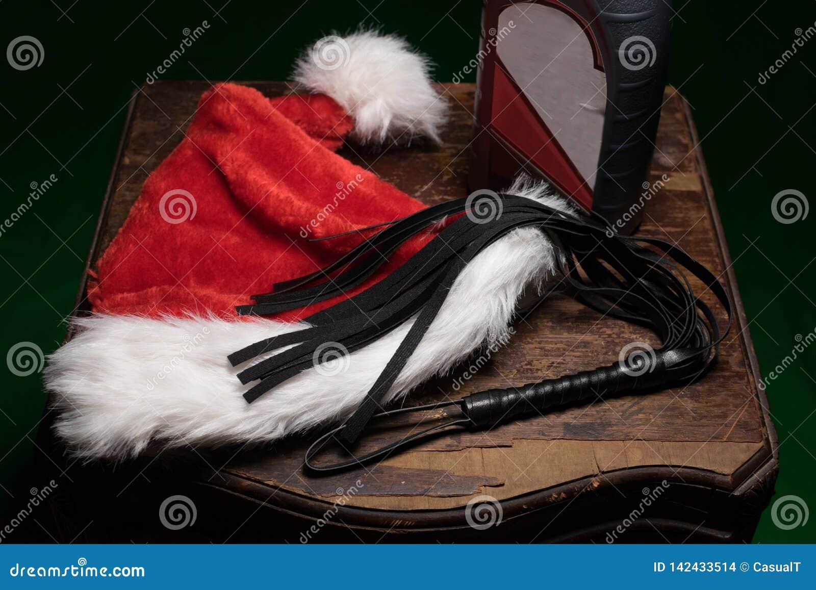 Un cappello rosso e bianco sfocato di Santa, una frusta nera e una bottiglia dell olio di motore, su un vecchio wodden la tavola,
