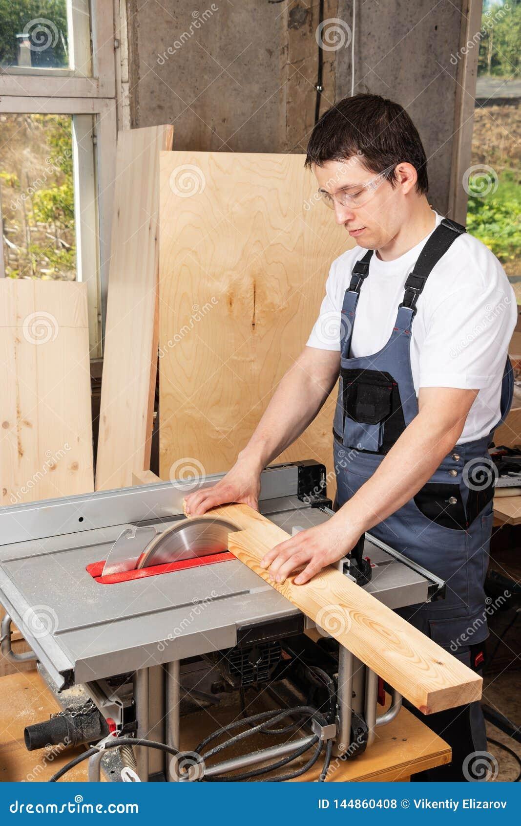 Un carpintero del hombre asierra a un tablero de madera en una máquina de la carpintería