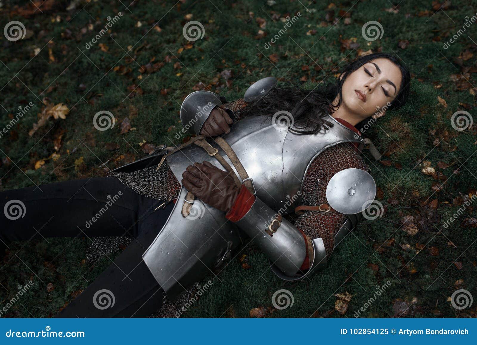 Un chainmail que lleva y una armadura de la muchacha hermosa del guerrero que mienten en la tierra en un bosque misterioso