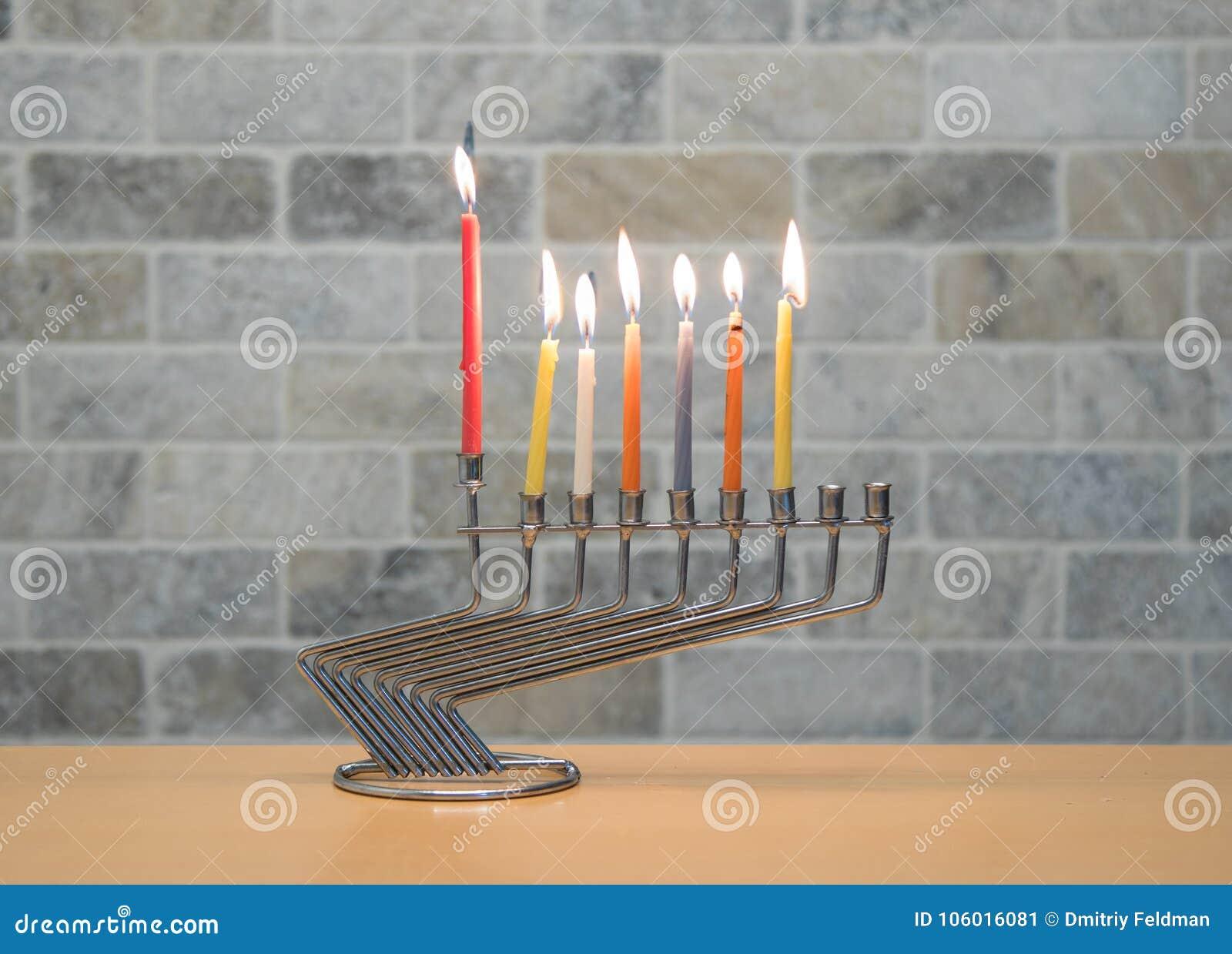 Un chandelier en métal pour la célébration de Hanoucca se tient avec les bougies allumées sur la table contre le contexte d un mu