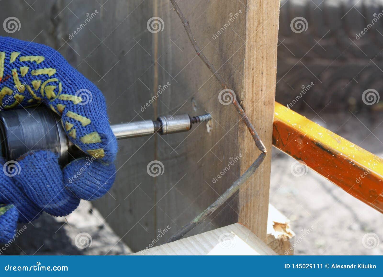 Un charpentier travaillant avec un tournevis électrique réparant une barrière en bois dans les gants protecteurs
