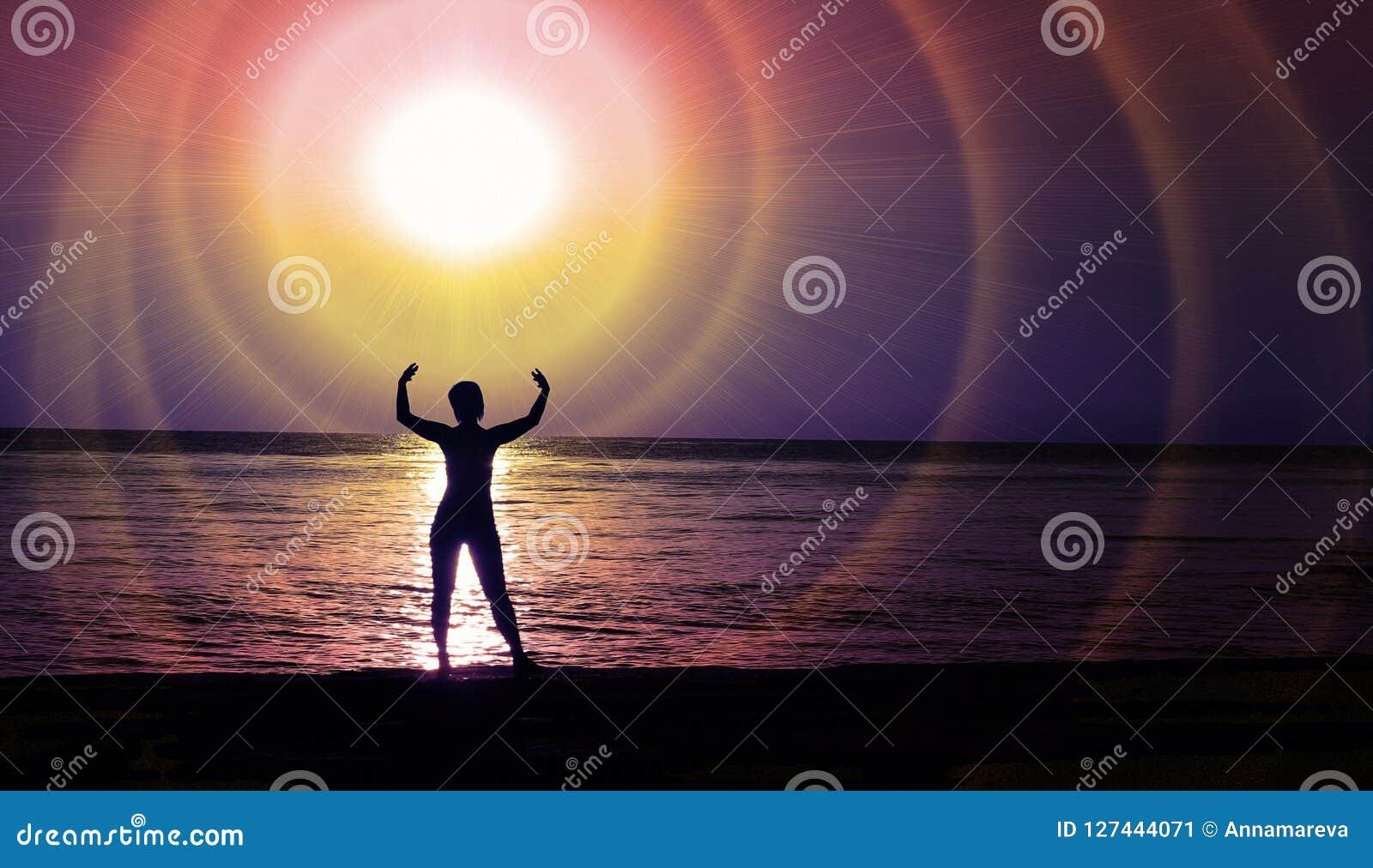 Un chiffre femelle à la lumière de la lueur cosmique d une étoile au-dessus de la côte de nuit