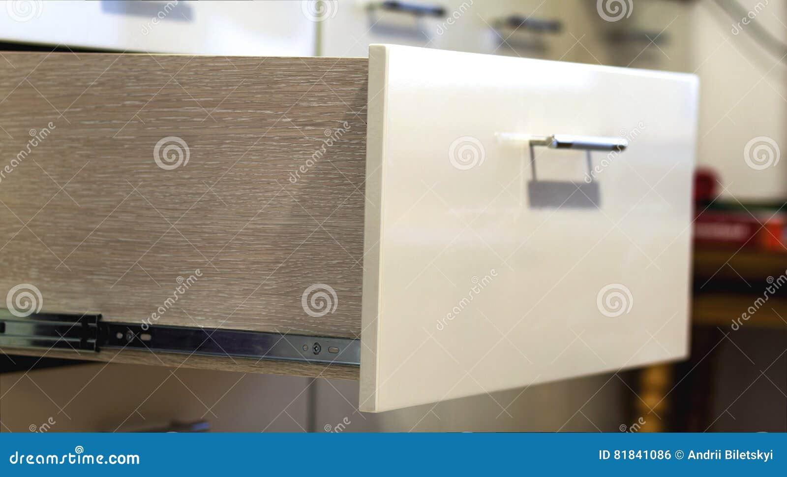Un cierre del detalle encima del tiro de un cajón elegante laminado de la cocina