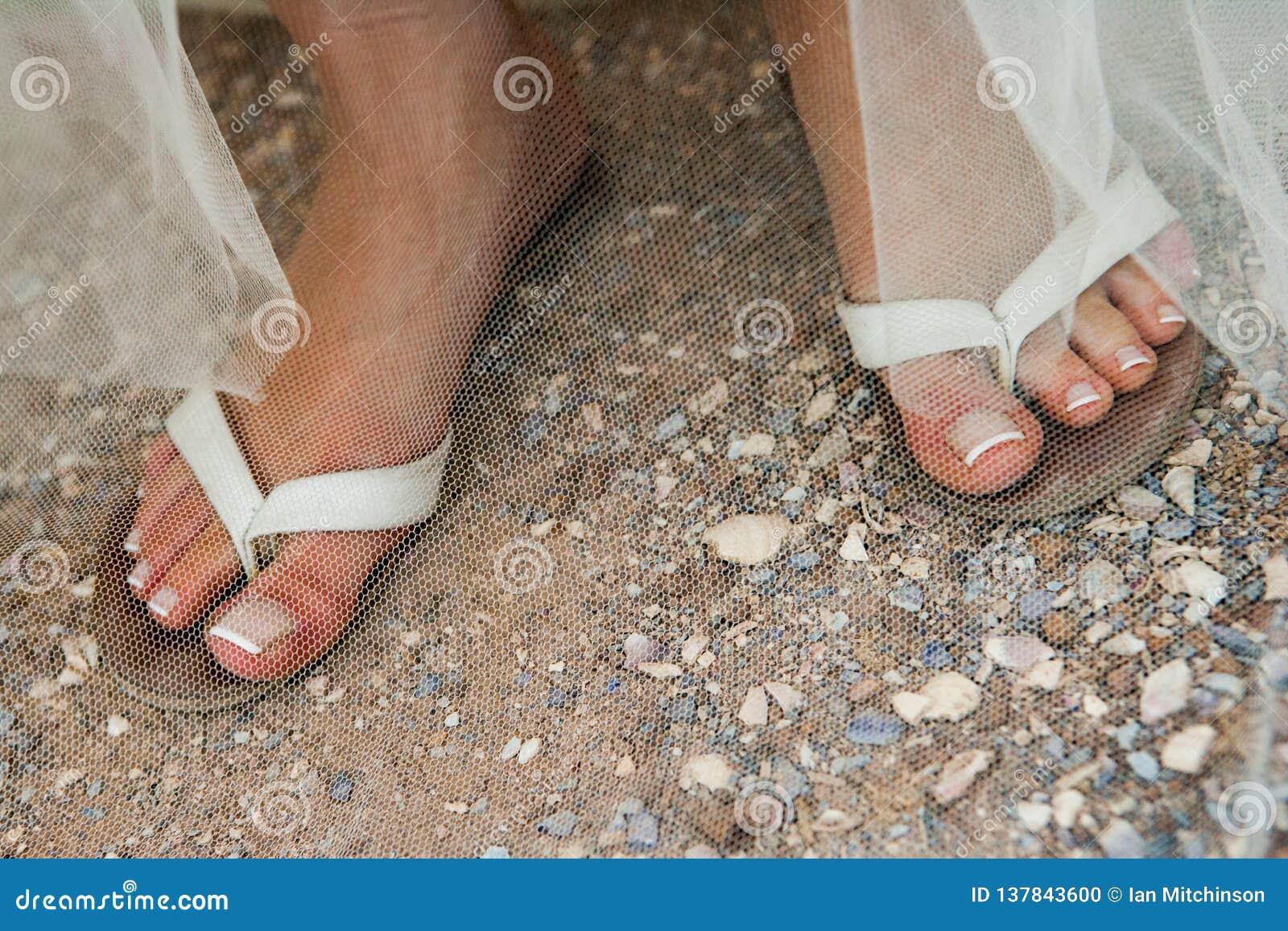Un cierre para arriba de las piernas de las novias en chancletas en una playa con los clavos manicured